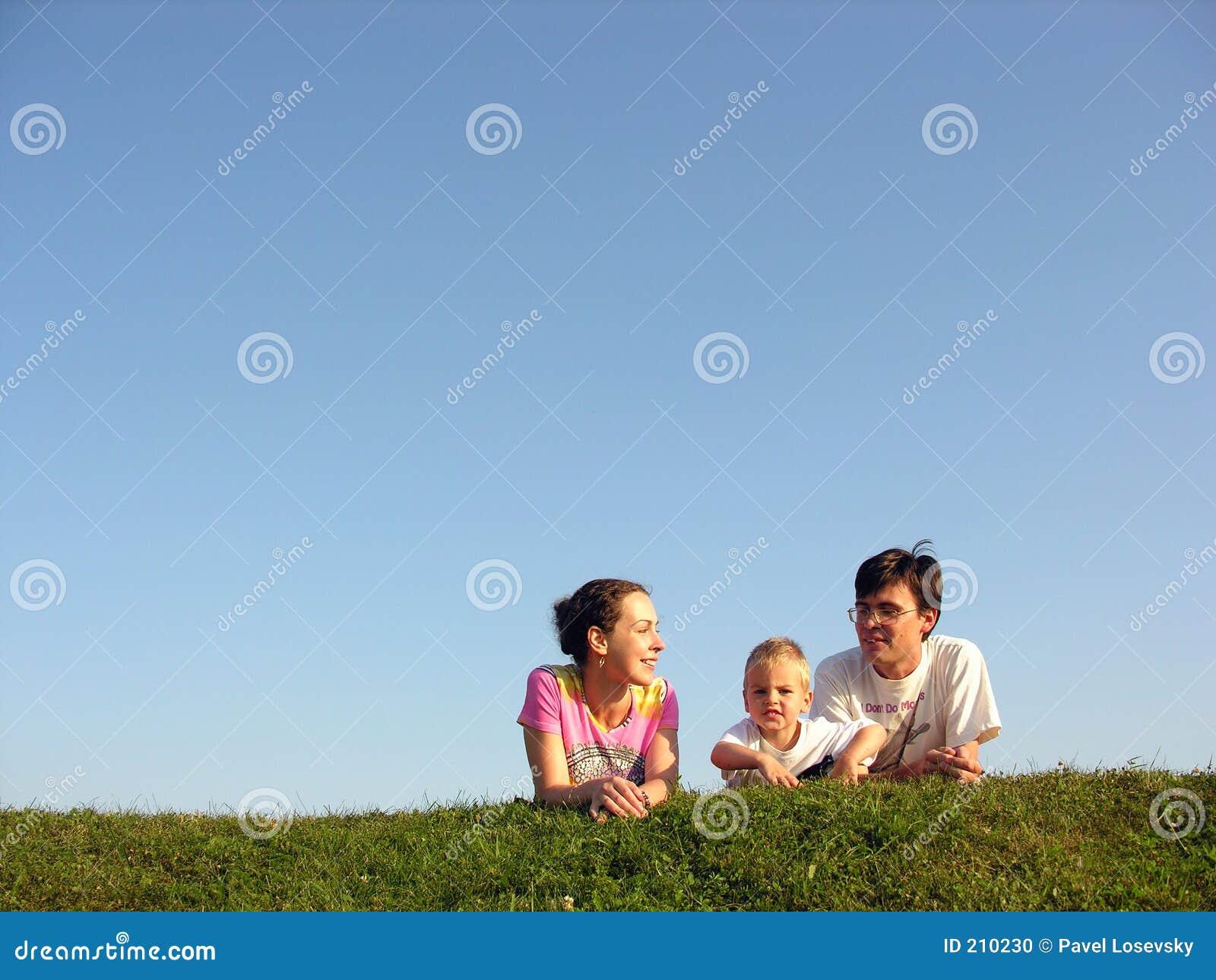 Family on herb under sky