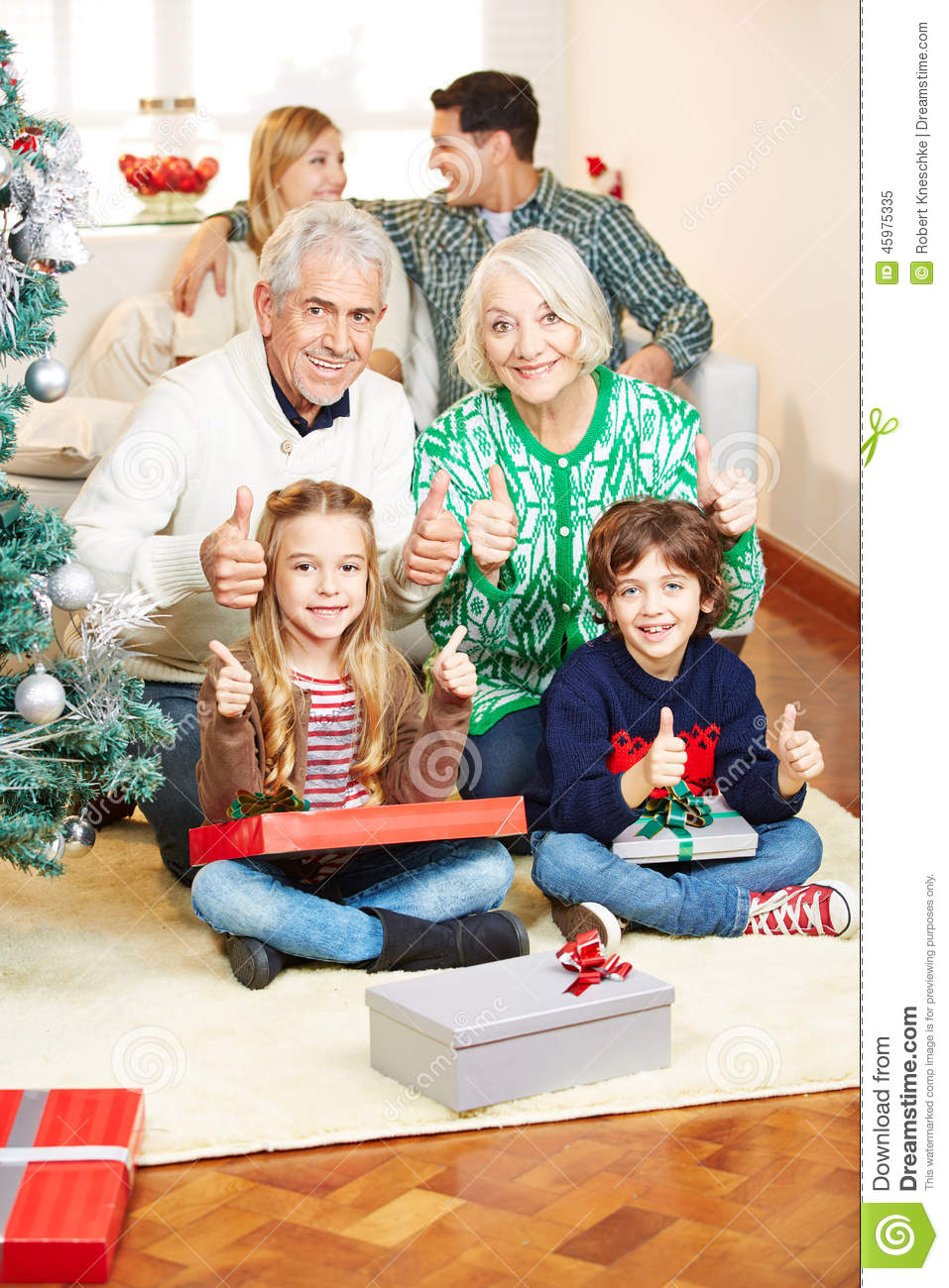 family holding thumbs up at christmas eve stock image