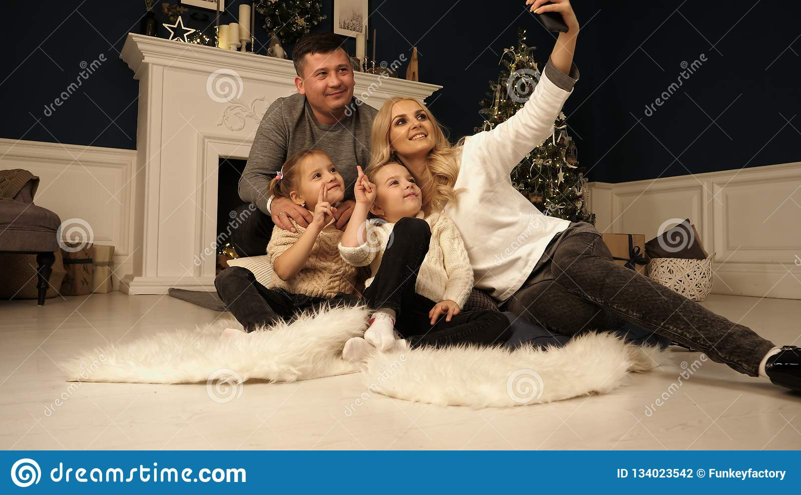 Family, holidays, technology and people - smiling mother, father and little girls making selfie with camera over