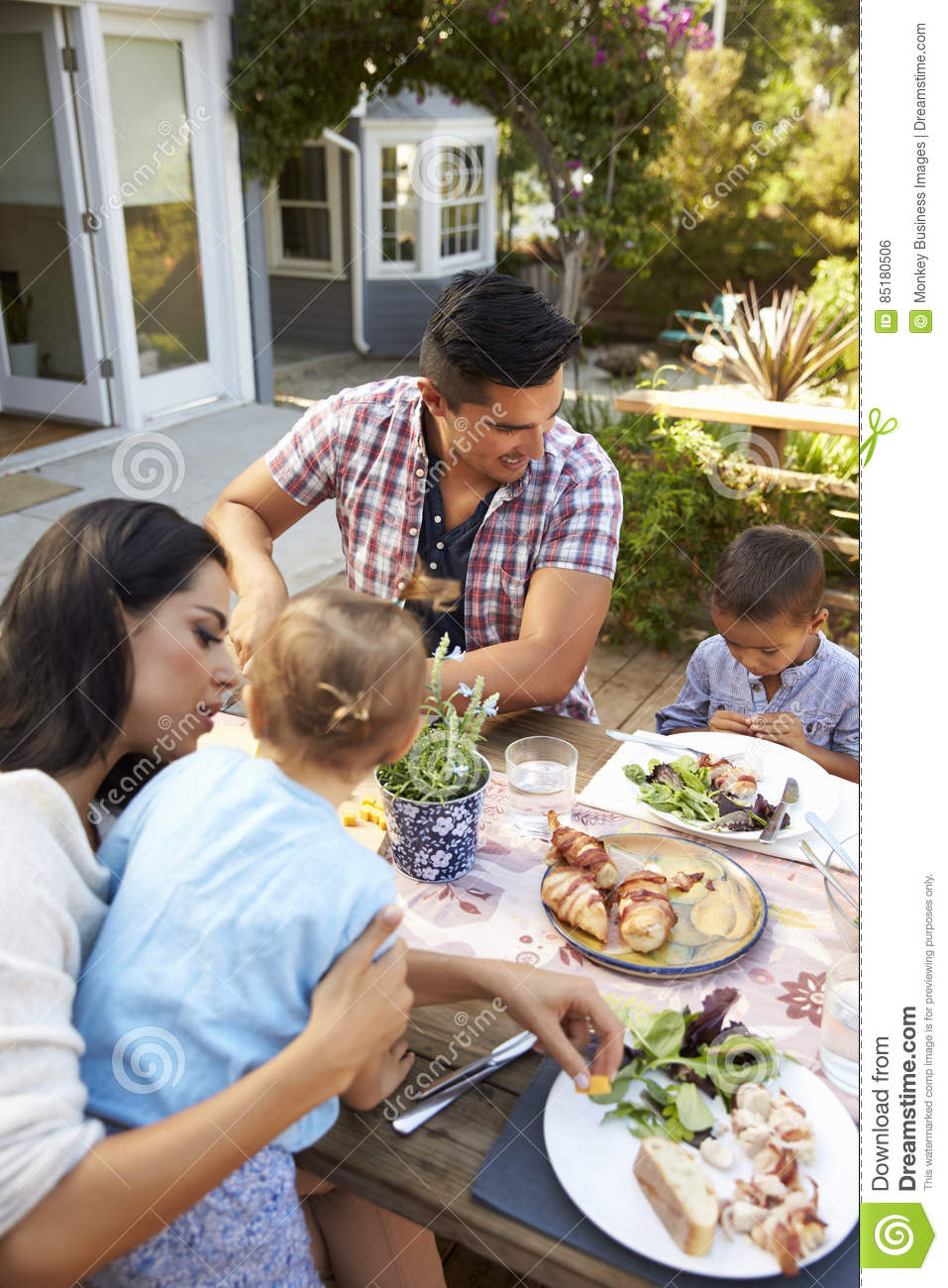 Family at home eating outdoor meal in garden together for Meal outdoors