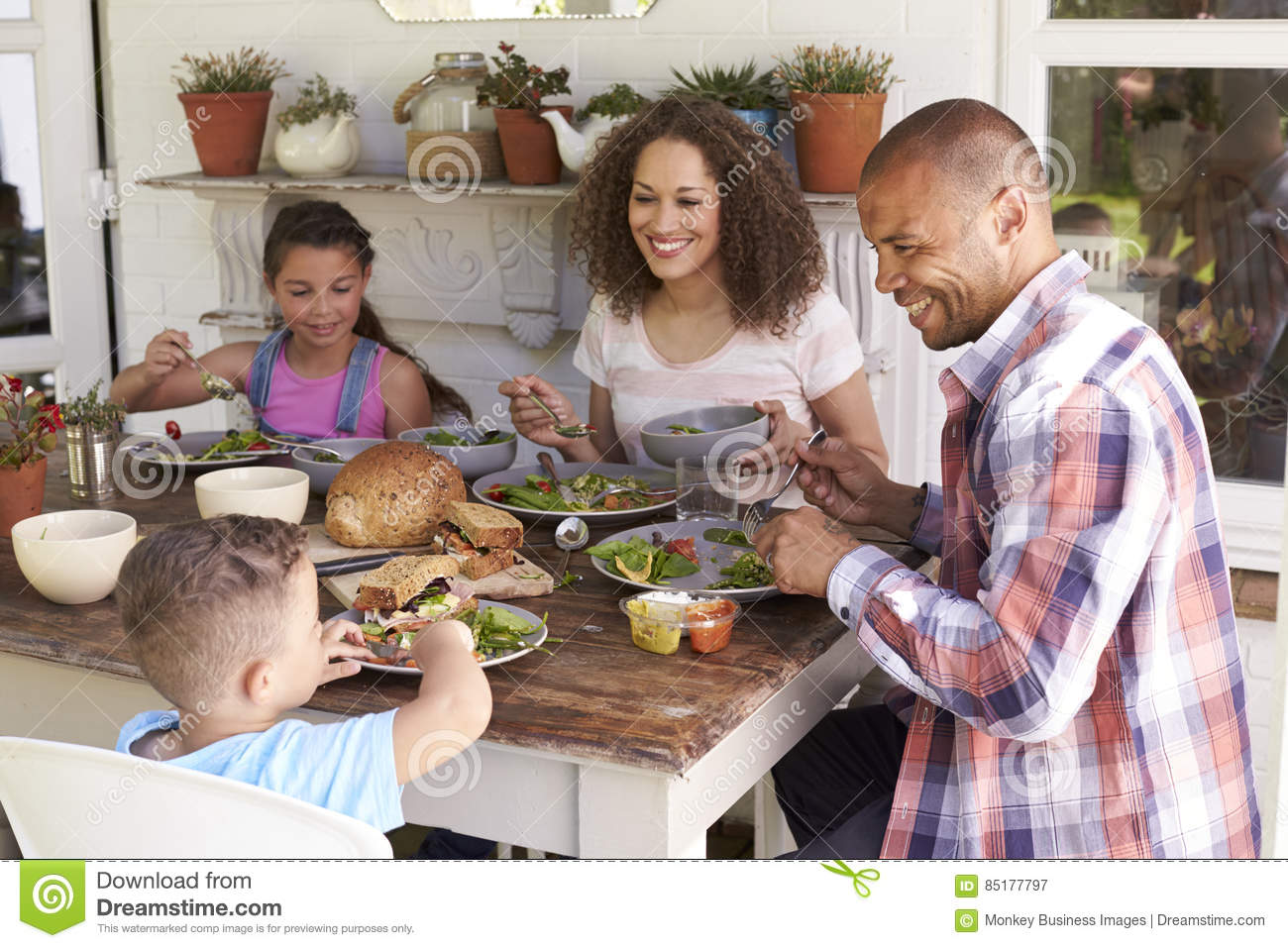 Family At Home Eating Outdoor Meal Together