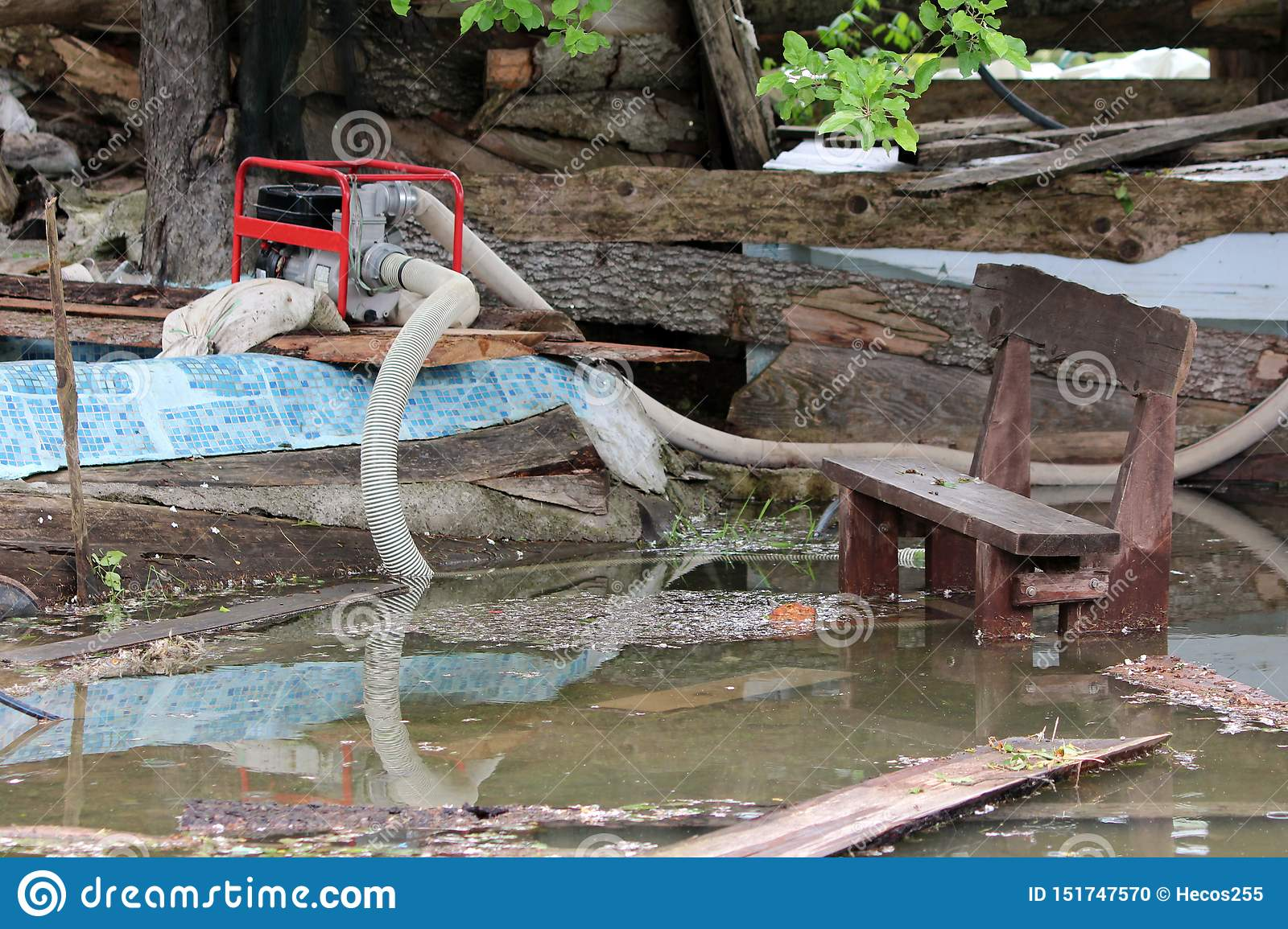 Family house backyard completely destroyed during natural disaster with industrial petrol water pump used to pump flood water next