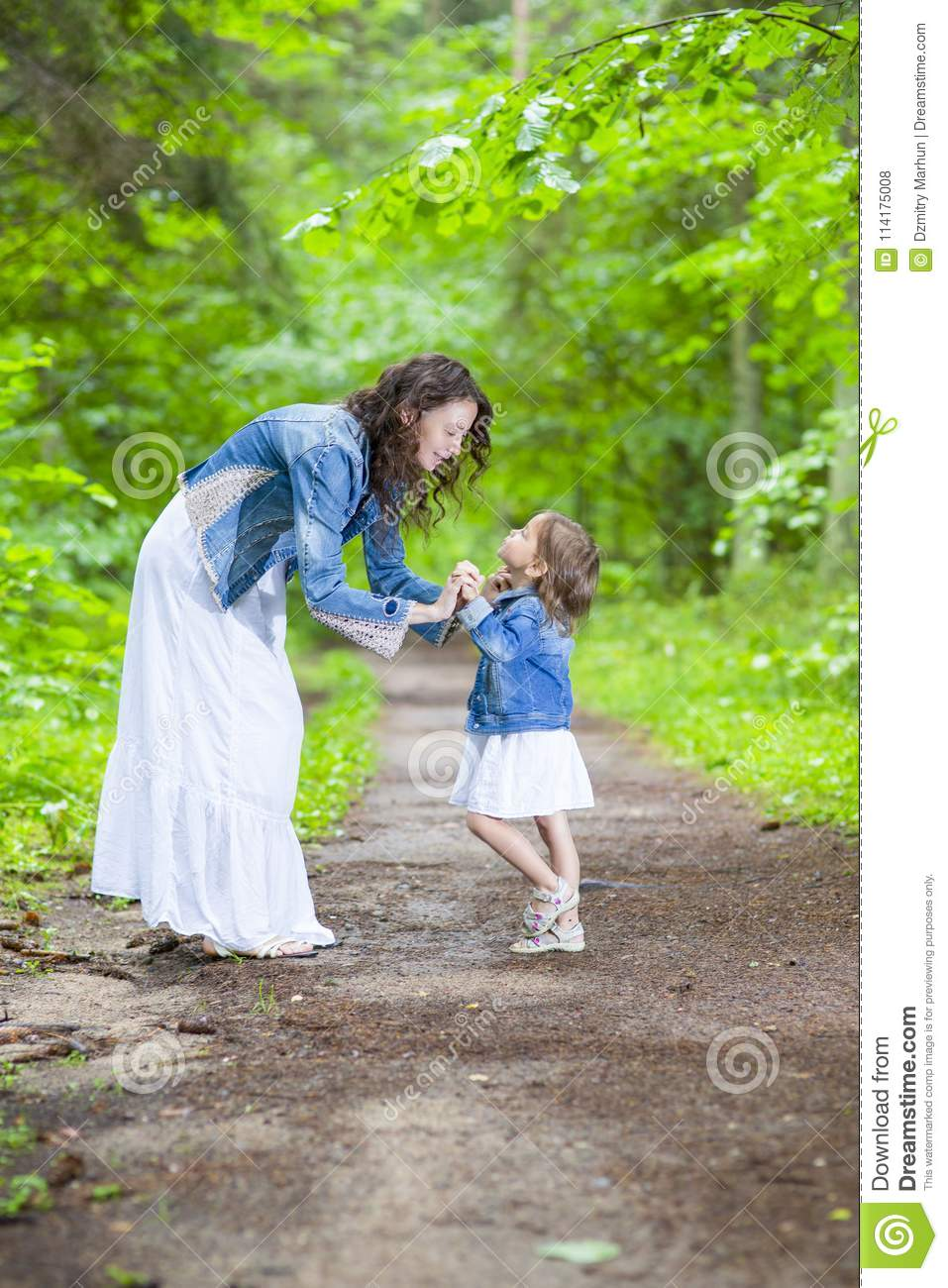 Family ideas and concepts happy mother and her little caucasian daughter posing with playful expression together in green summer forest