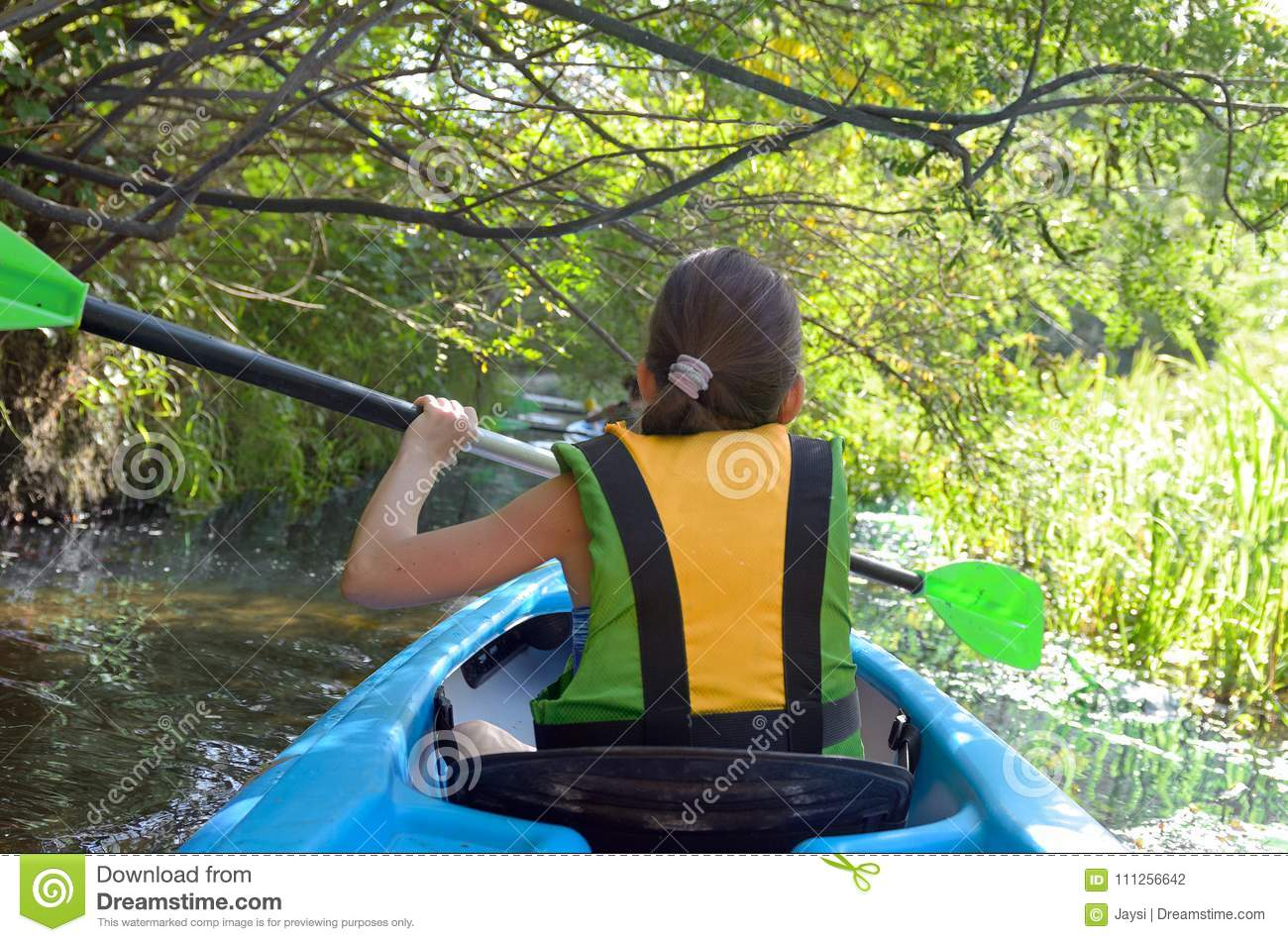 Family kayaking, child paddling in kayak on river canoe tour, kid on active autumn weekend and vacation, sport and fitness