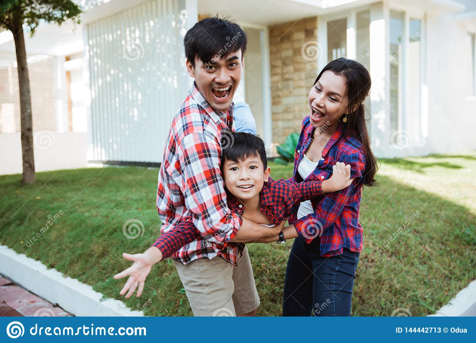 Family and kid enjoy playing together in front of their house