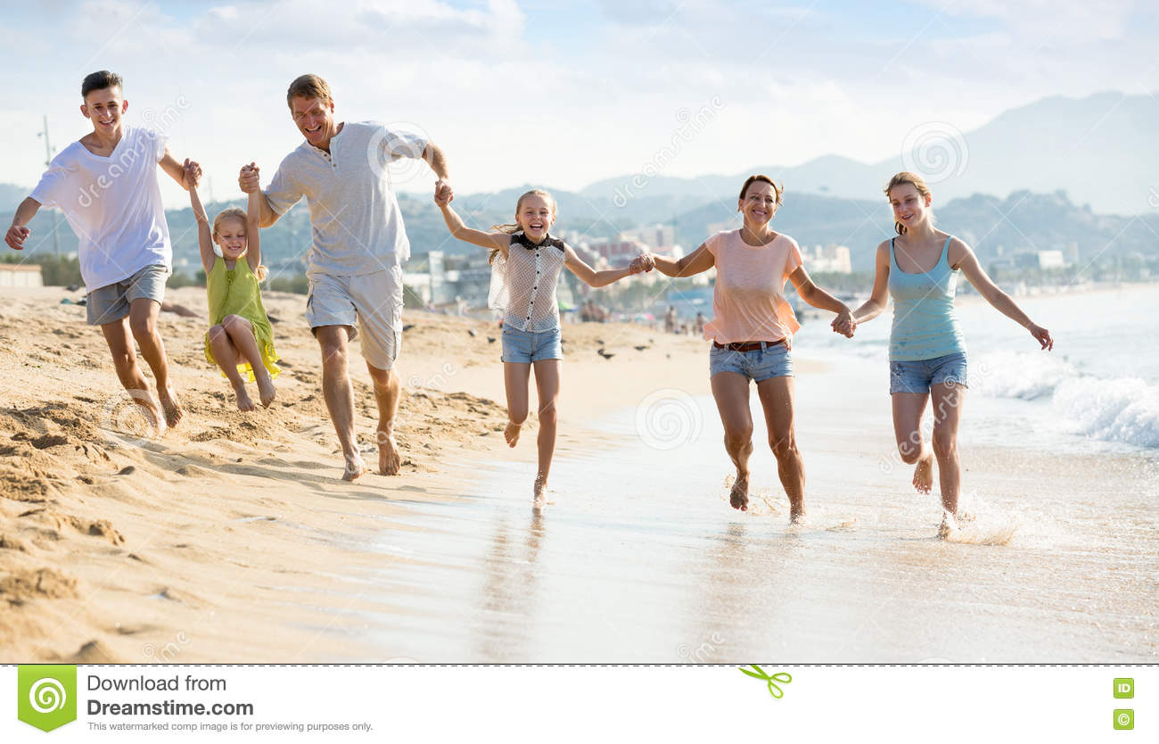 Family With Kids Happily Running Together On Beach