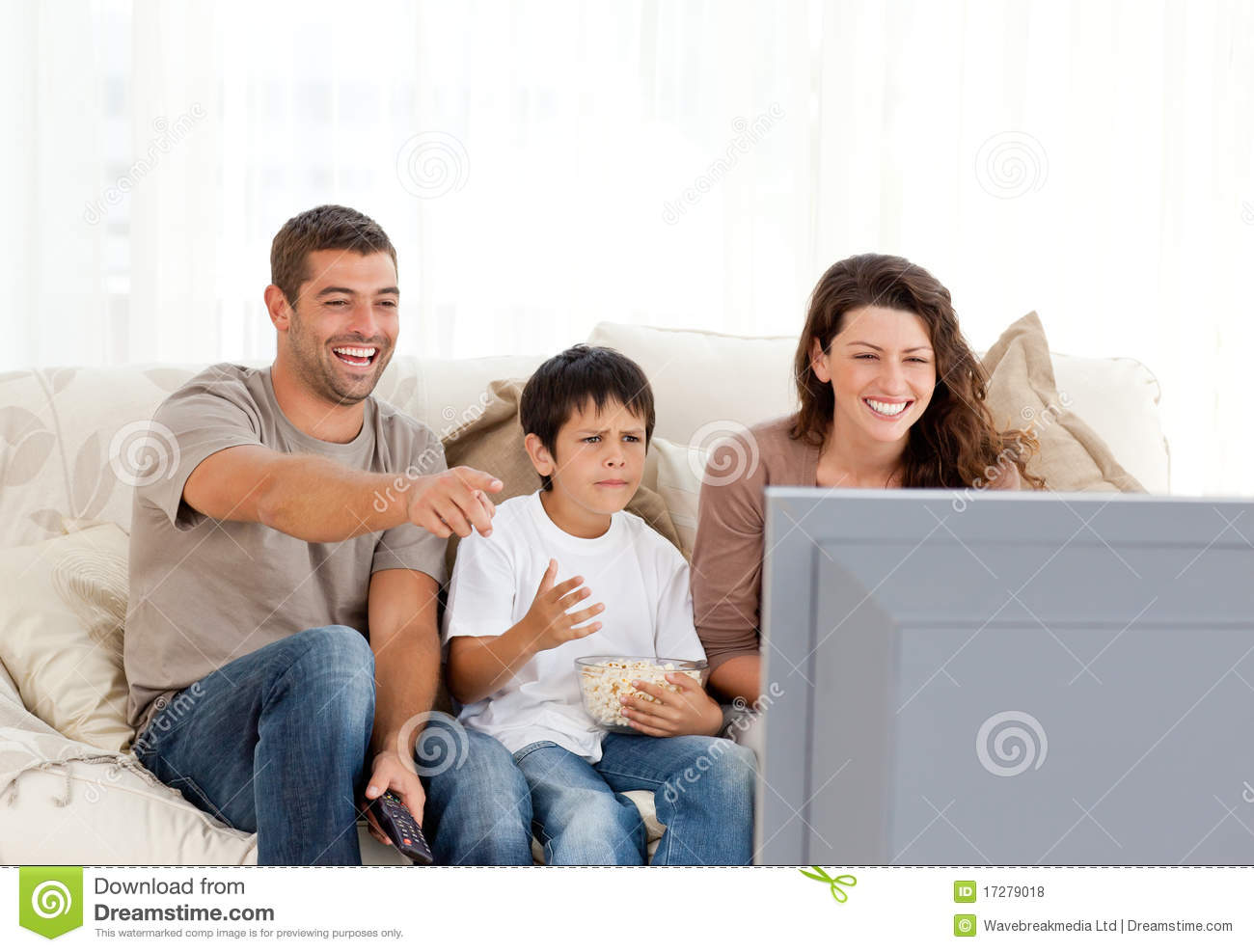 family laughing while watching television together royalty