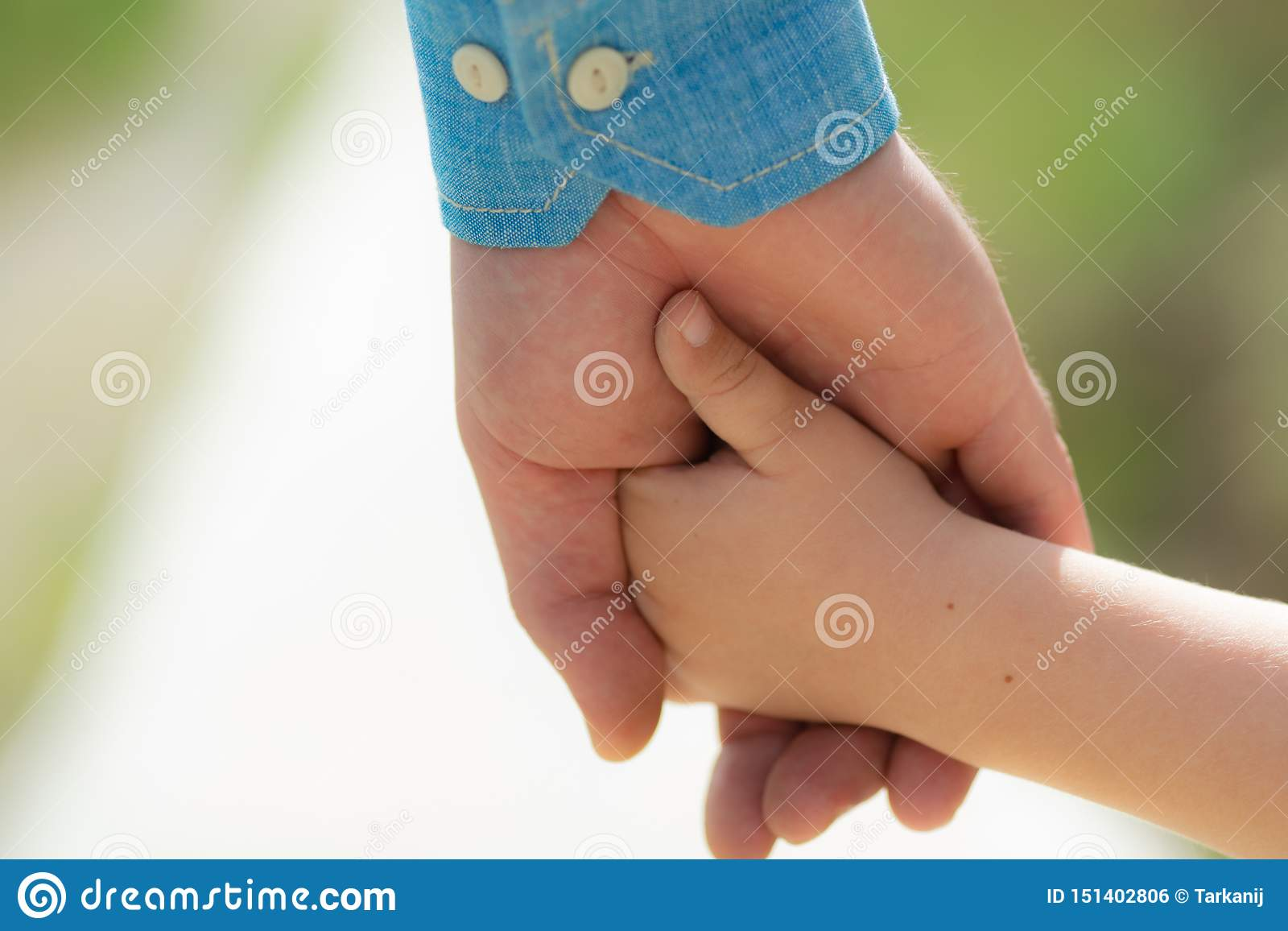 Family. Little child holding hands with his father outdoors, closeup. Family time. Closeup of two touching hands of