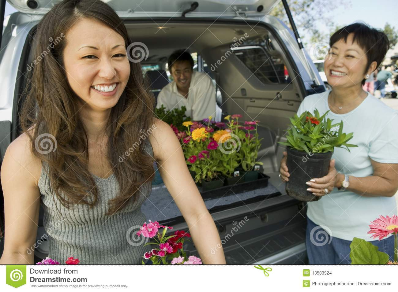 Family loading flowers into SUV