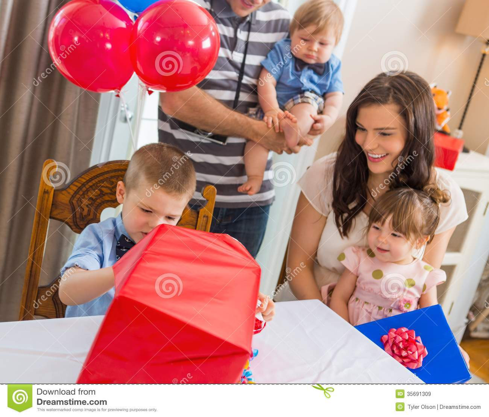 Family Looking At Birthday Boy Opening Gift Box Royalty