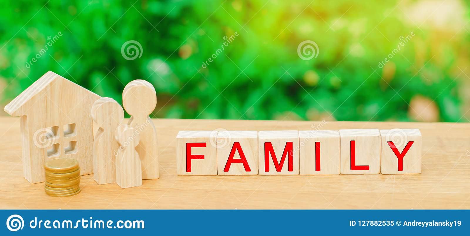 The family with money is standing near their house. concept of wealth life and a happy well-endowed. inscription `family` on woode