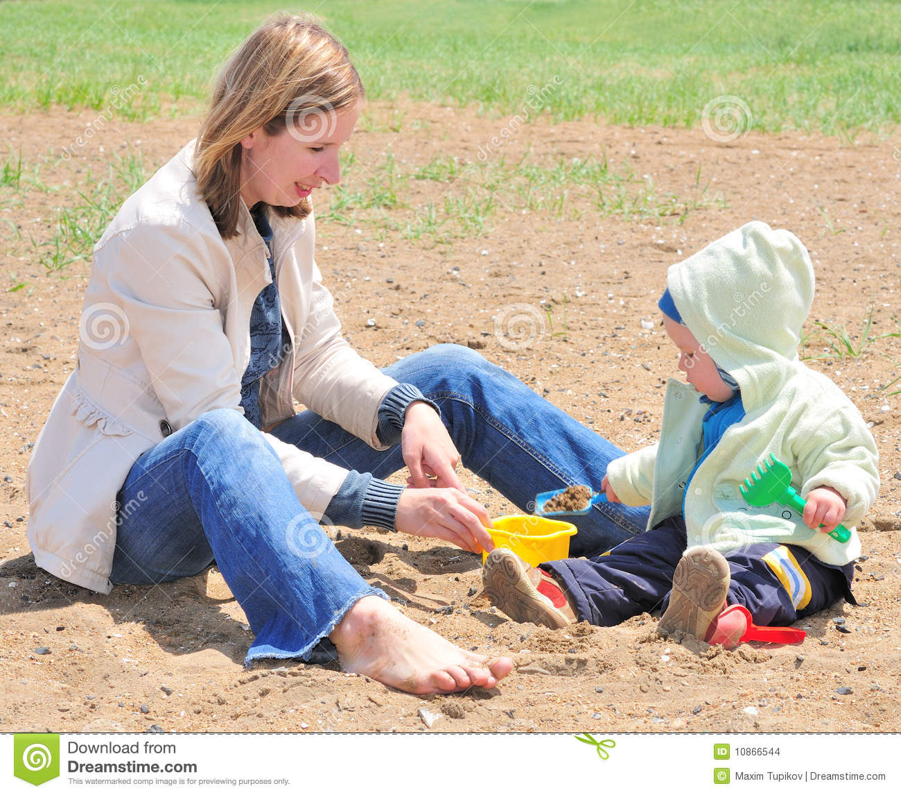 Family Enjoying Time Together On Beautiful Foggy Beach: Family Of Mother Playing With Baby In The Sand Stock Photo