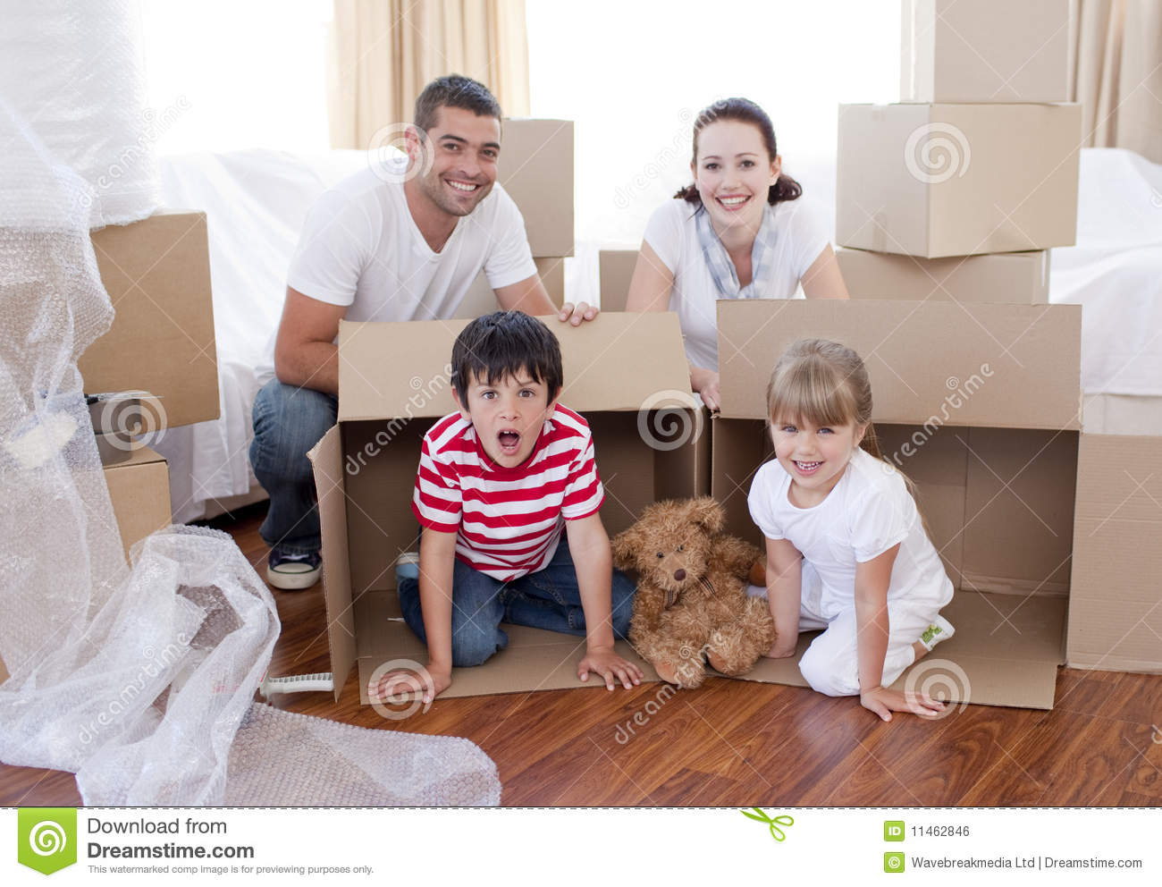 Family Moving House With Boxes Around Stock Photo Image