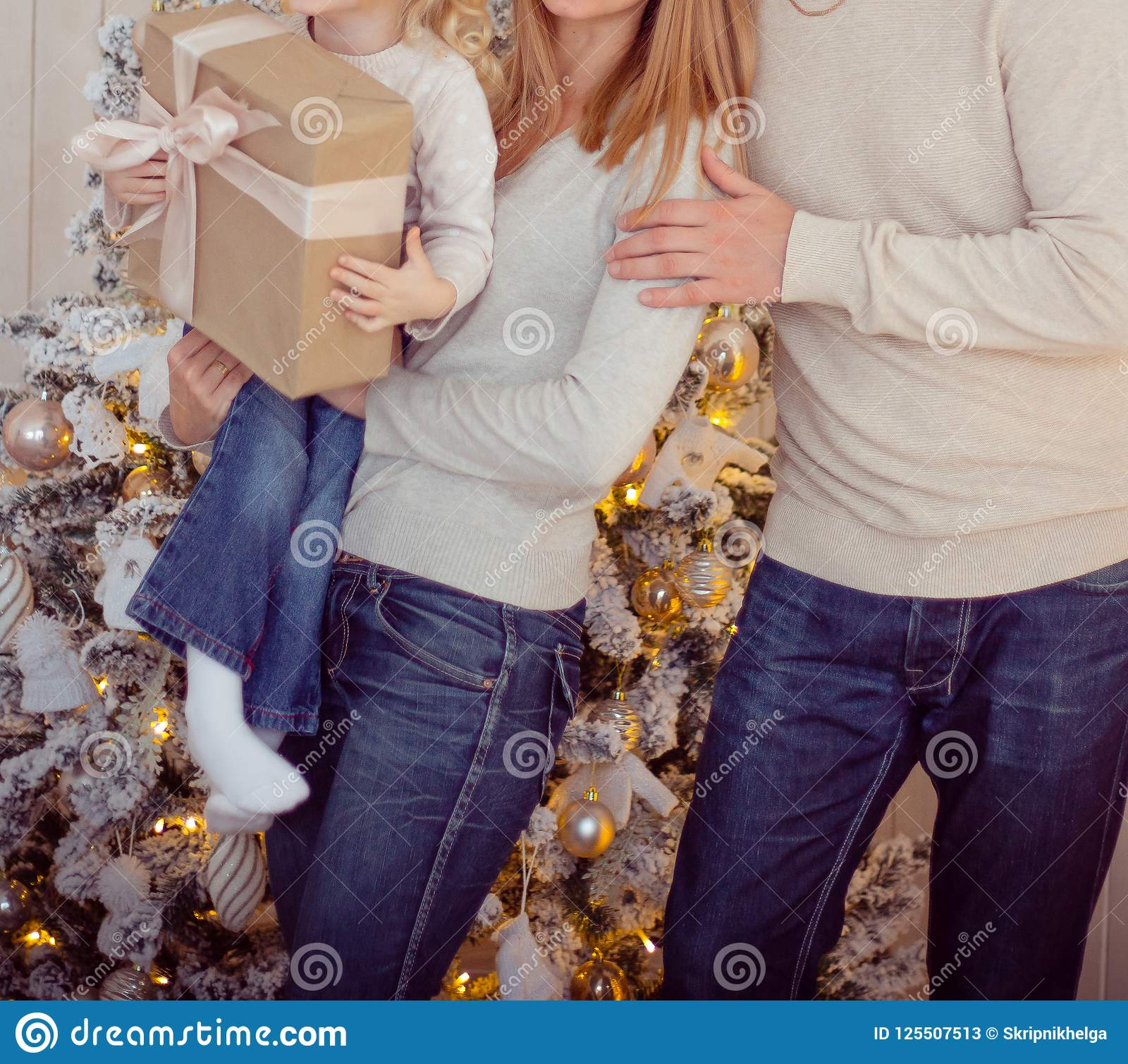 Family Near The Christmas Tree, Hugs And Keeps Gifts, Mom, Dad And ...
