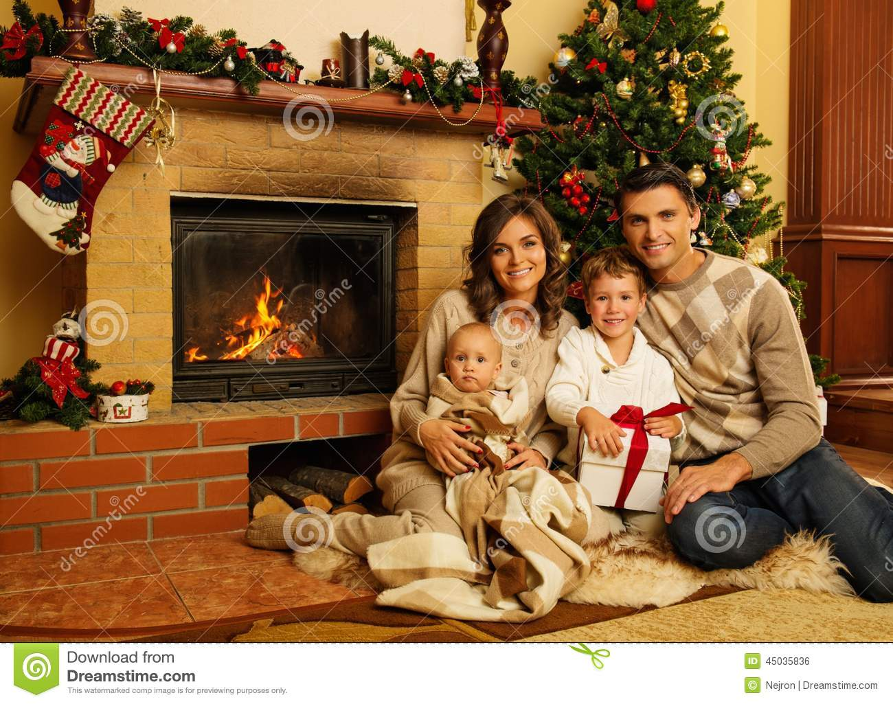 Family near fireplace in Christmas decorated house interior with gift ...