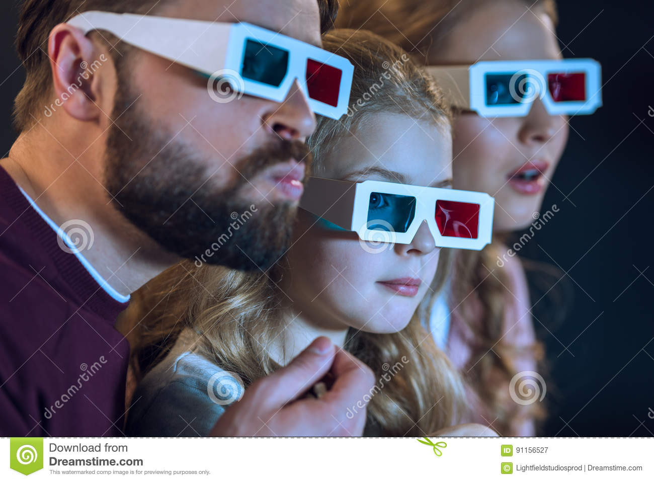 dea0322b95f Close-up view of family with one child wearing 3d glasses and watching movie