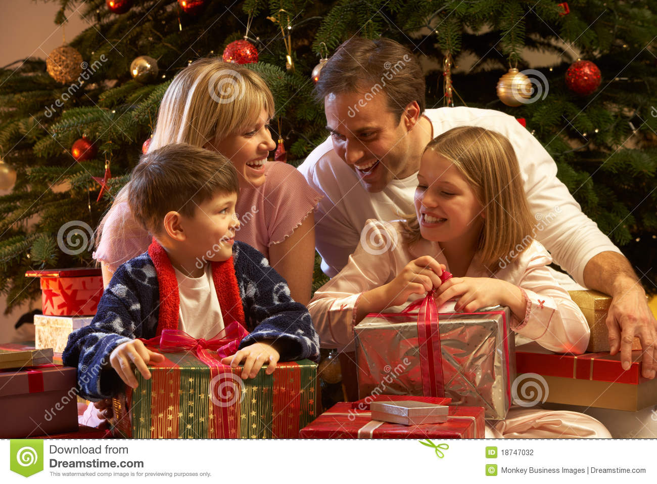 Family Opening Christmas Present In Front Of Tree Stock ...