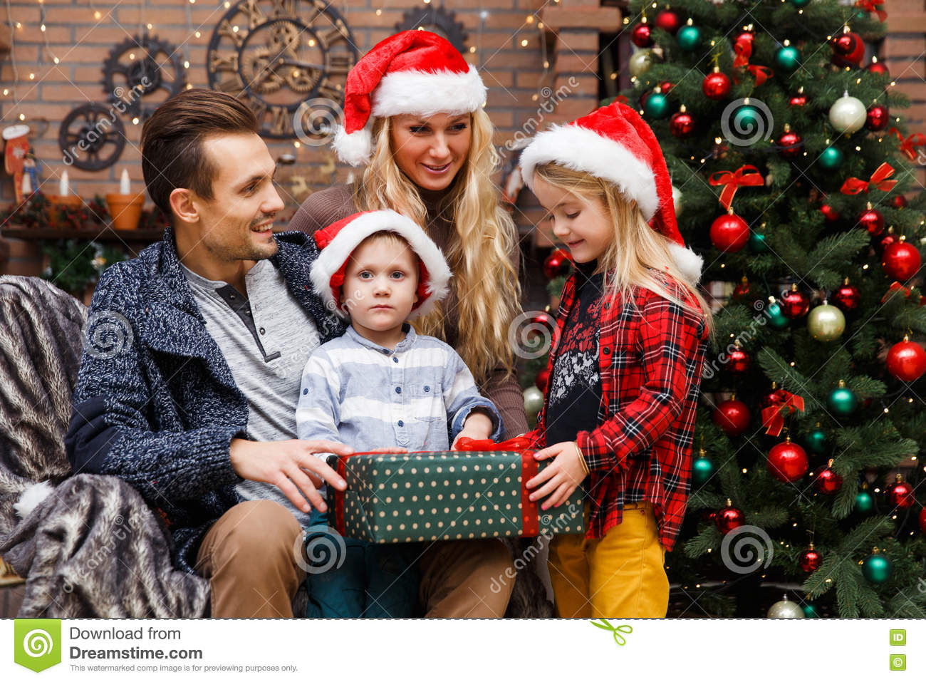 Family opening gifts at tree