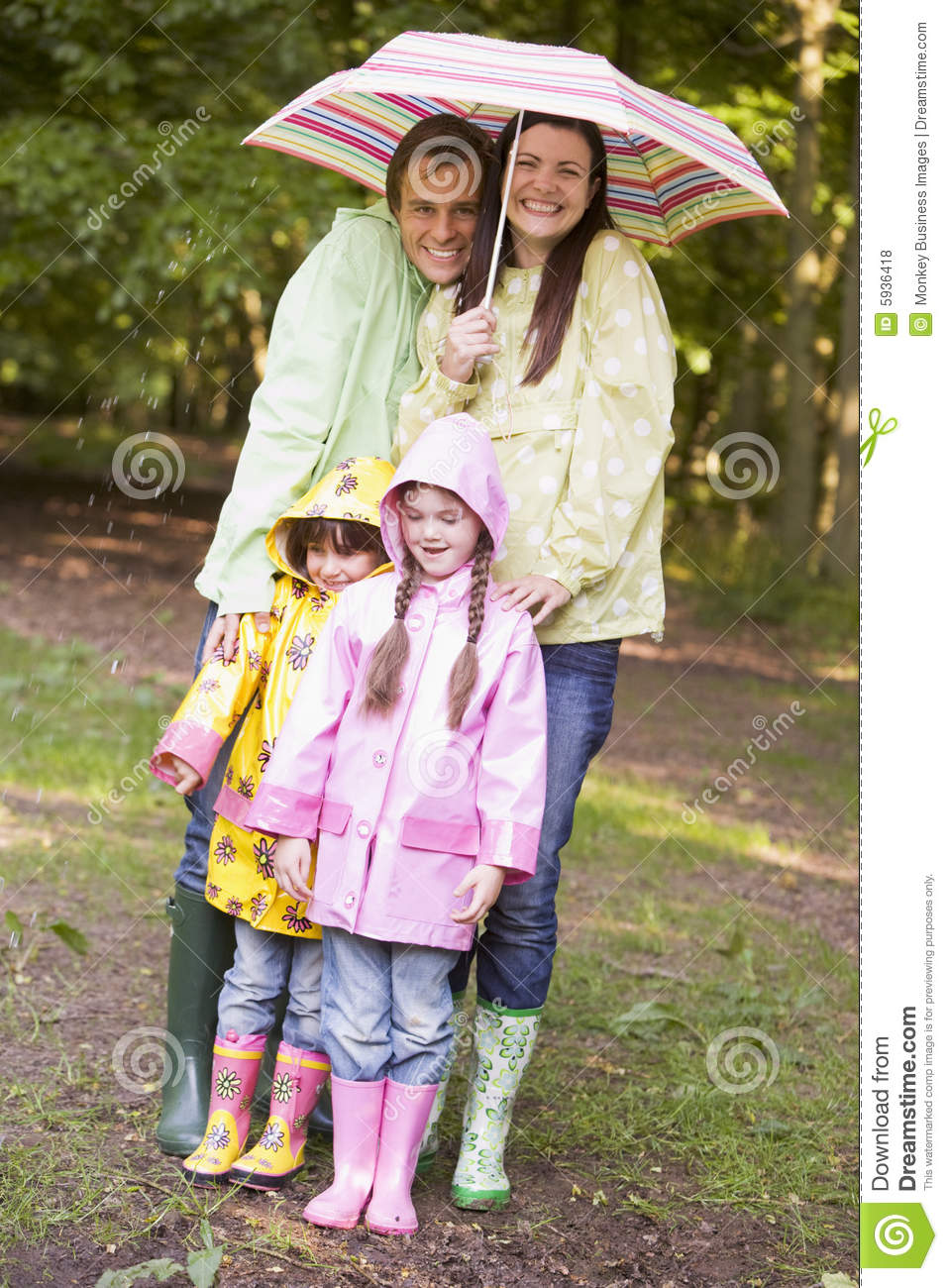 Family Outdoors In Rain With Umbrella Smiling Stock Photo