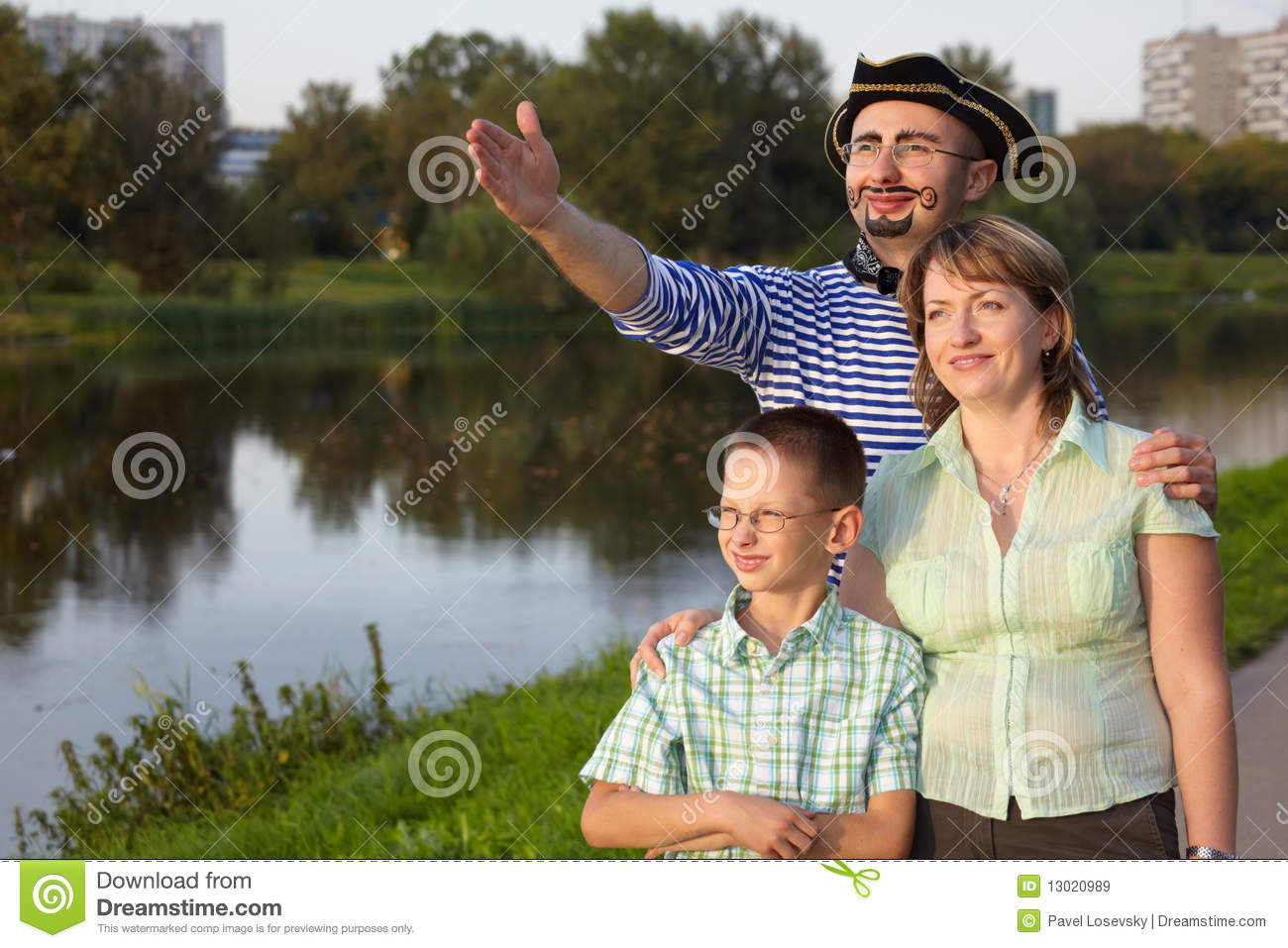 Family in park near pond: man in pirat suit