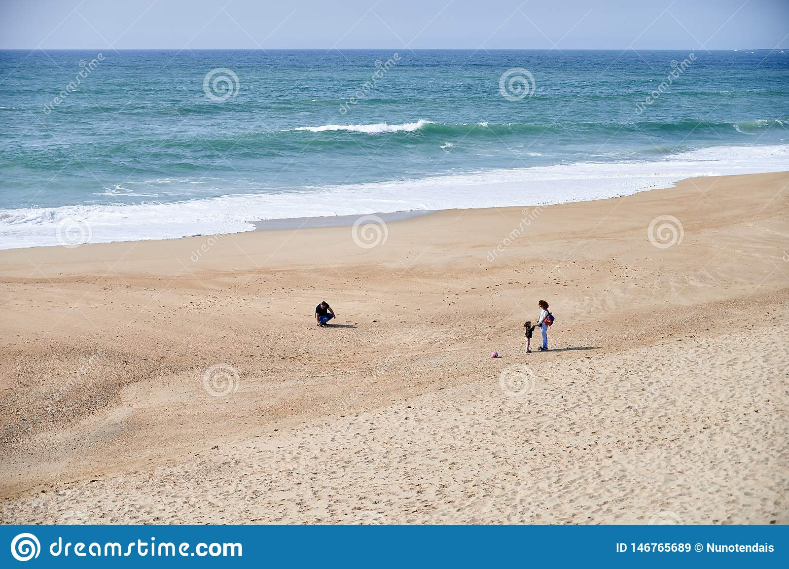 Family playing on the beach on spring