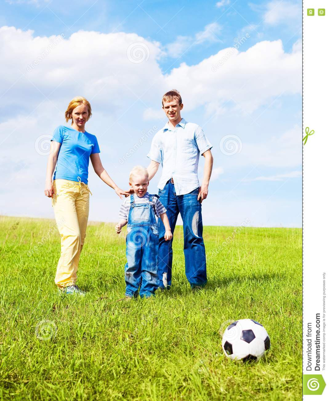 Happy young family playing football outdoor on a summer day Family Football