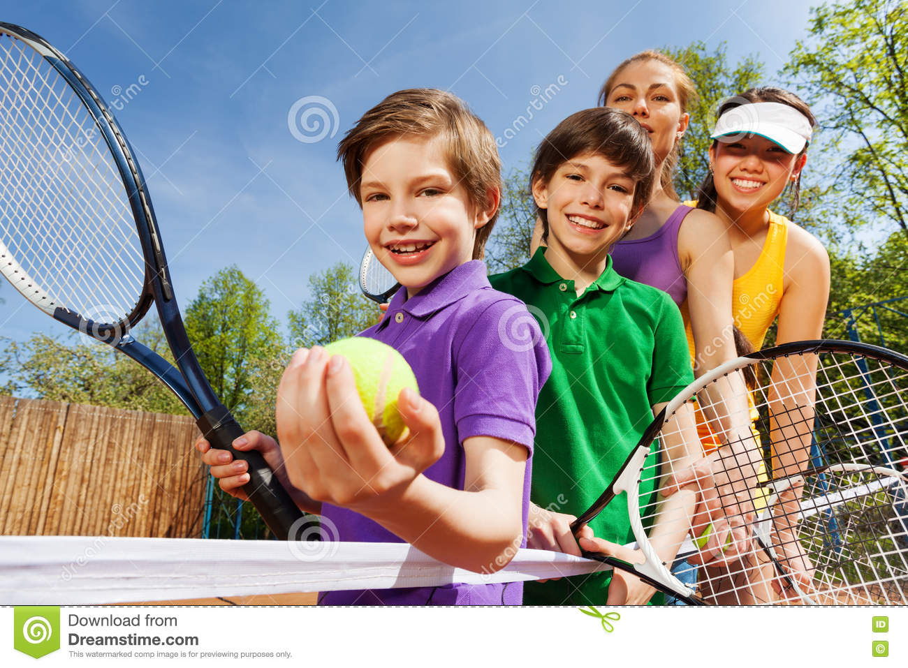 Family playing tennis holding rackets and ball