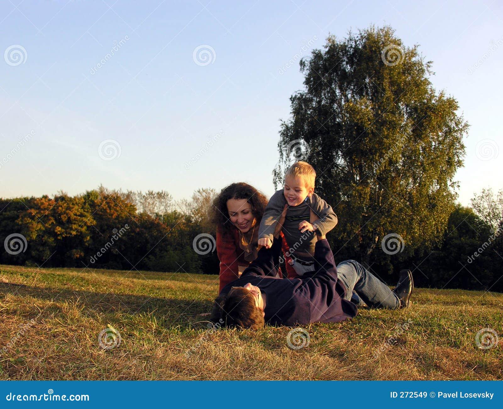 Family plays autumn on sundown on glade