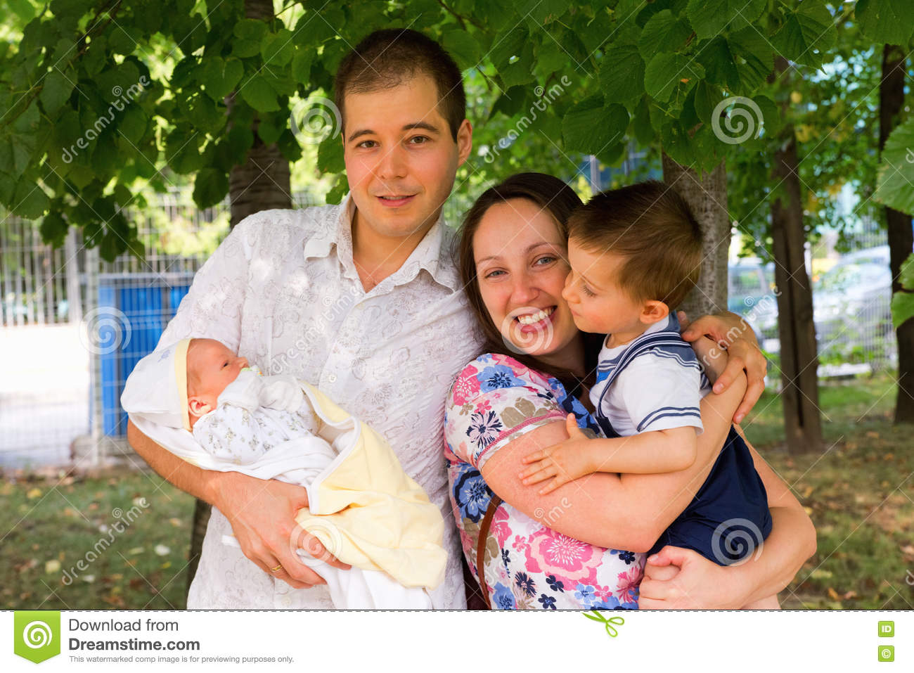 Family portrait of husband wife 1 year old kid and newborn baby boy shot outdoors