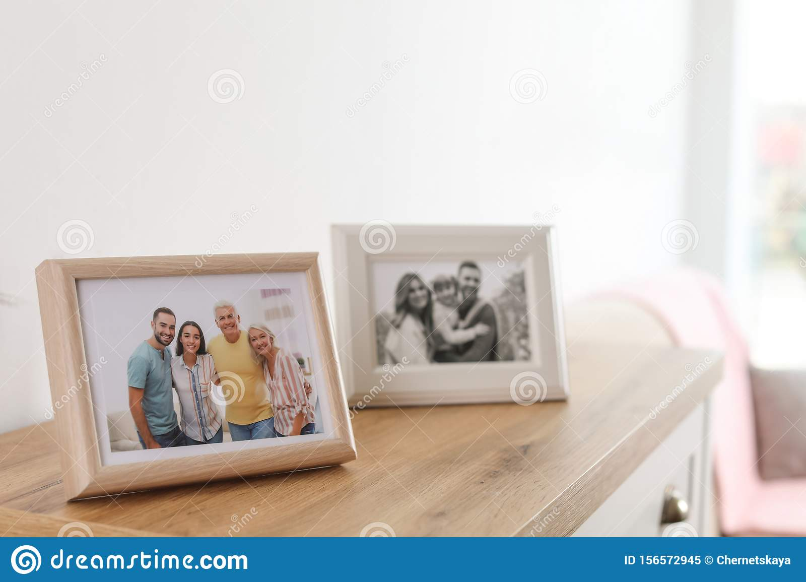Family portraits in frames on cabinet