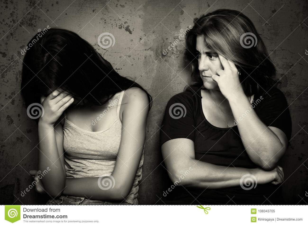 Teenage girl cries next to her angry and worried mother