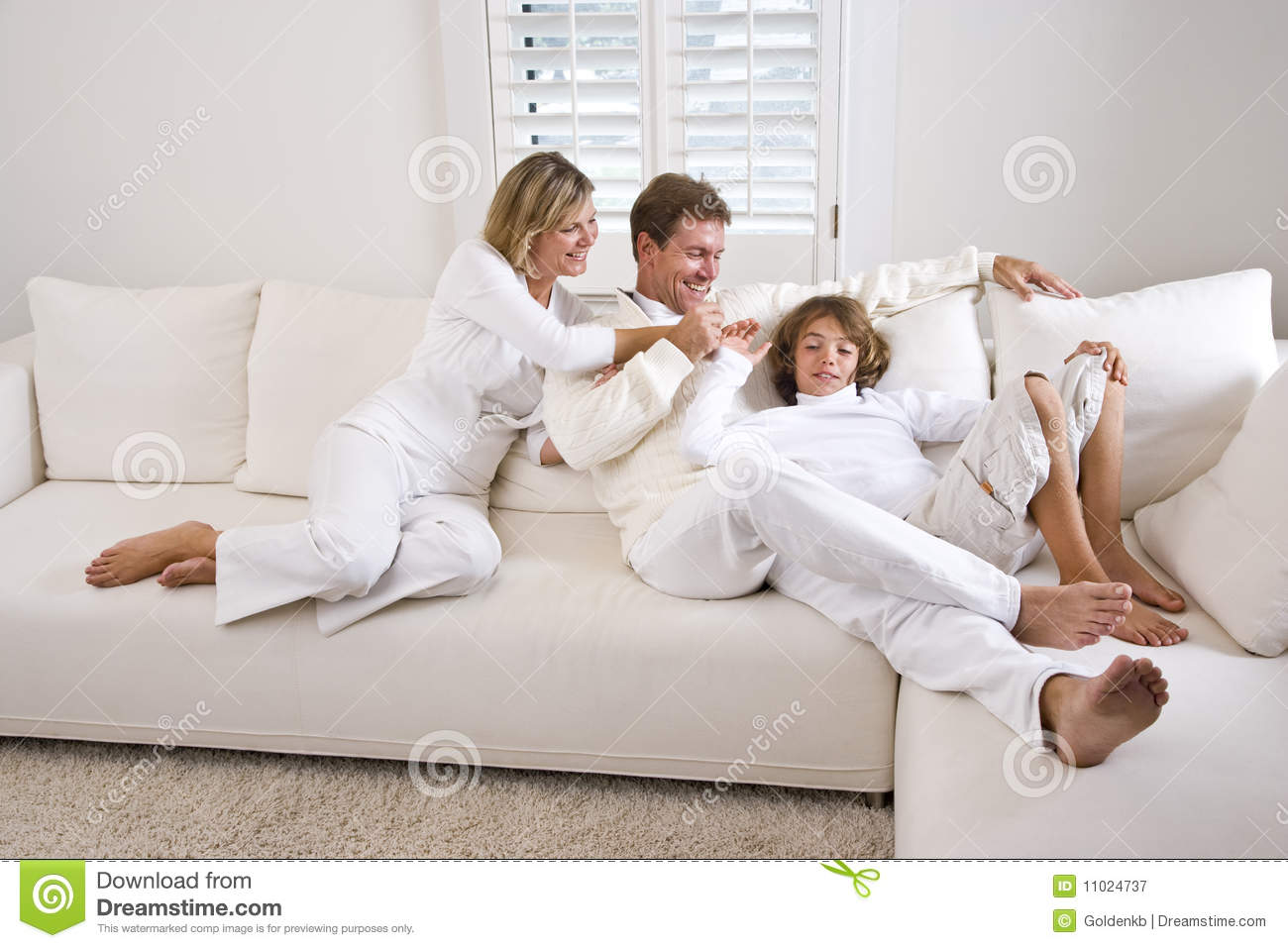 family relaxing at home on white living room sofa stock. Black Bedroom Furniture Sets. Home Design Ideas