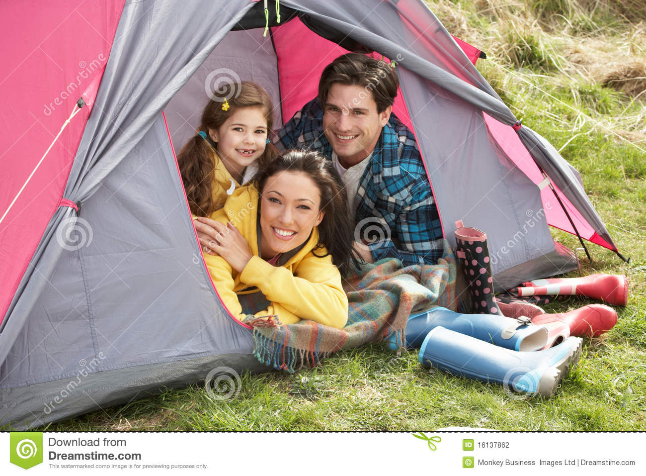 Family Relaxing Inside Tent On Camping Holiday