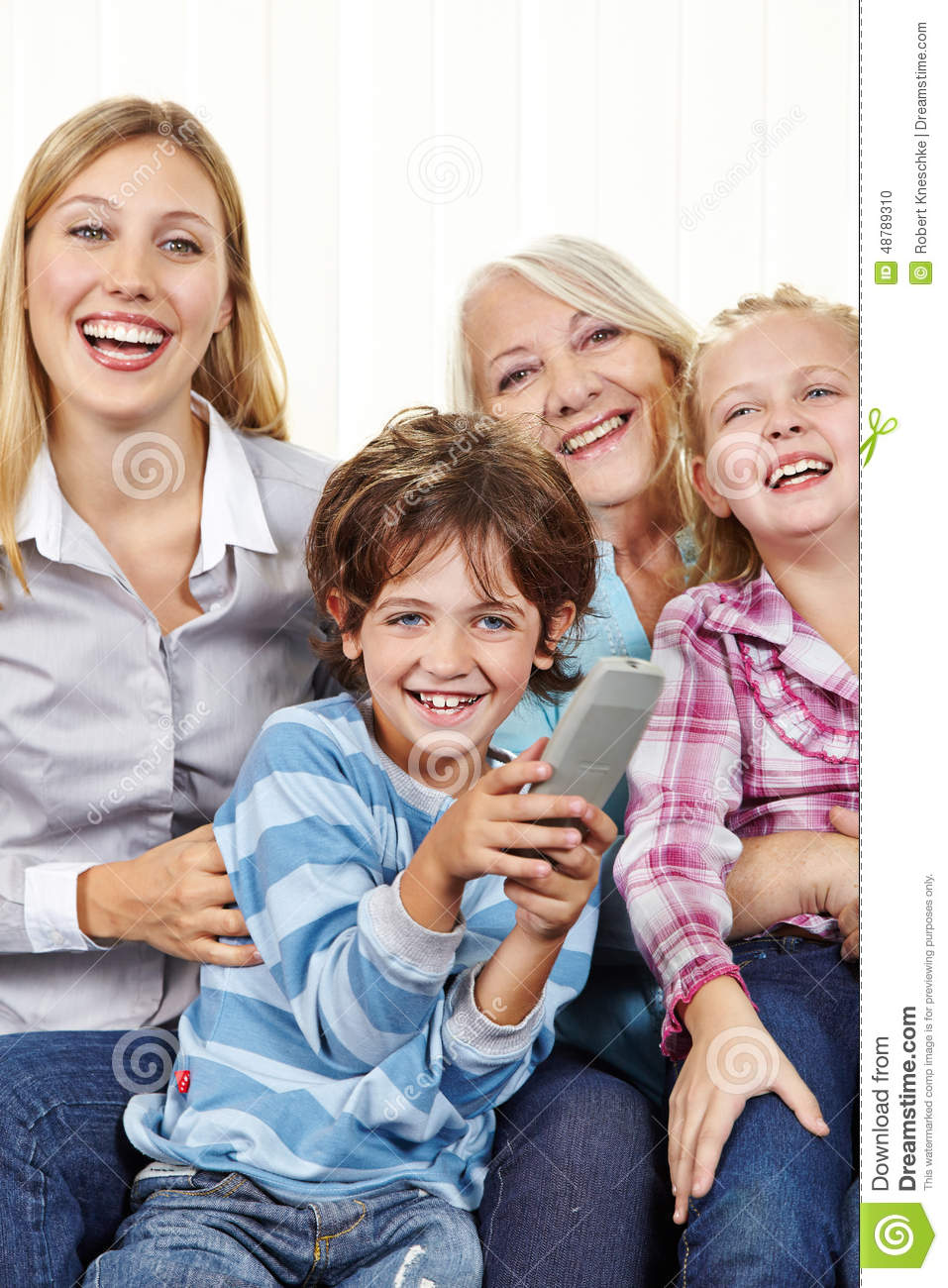 Family With Remote Control Watching TV Stock Photo