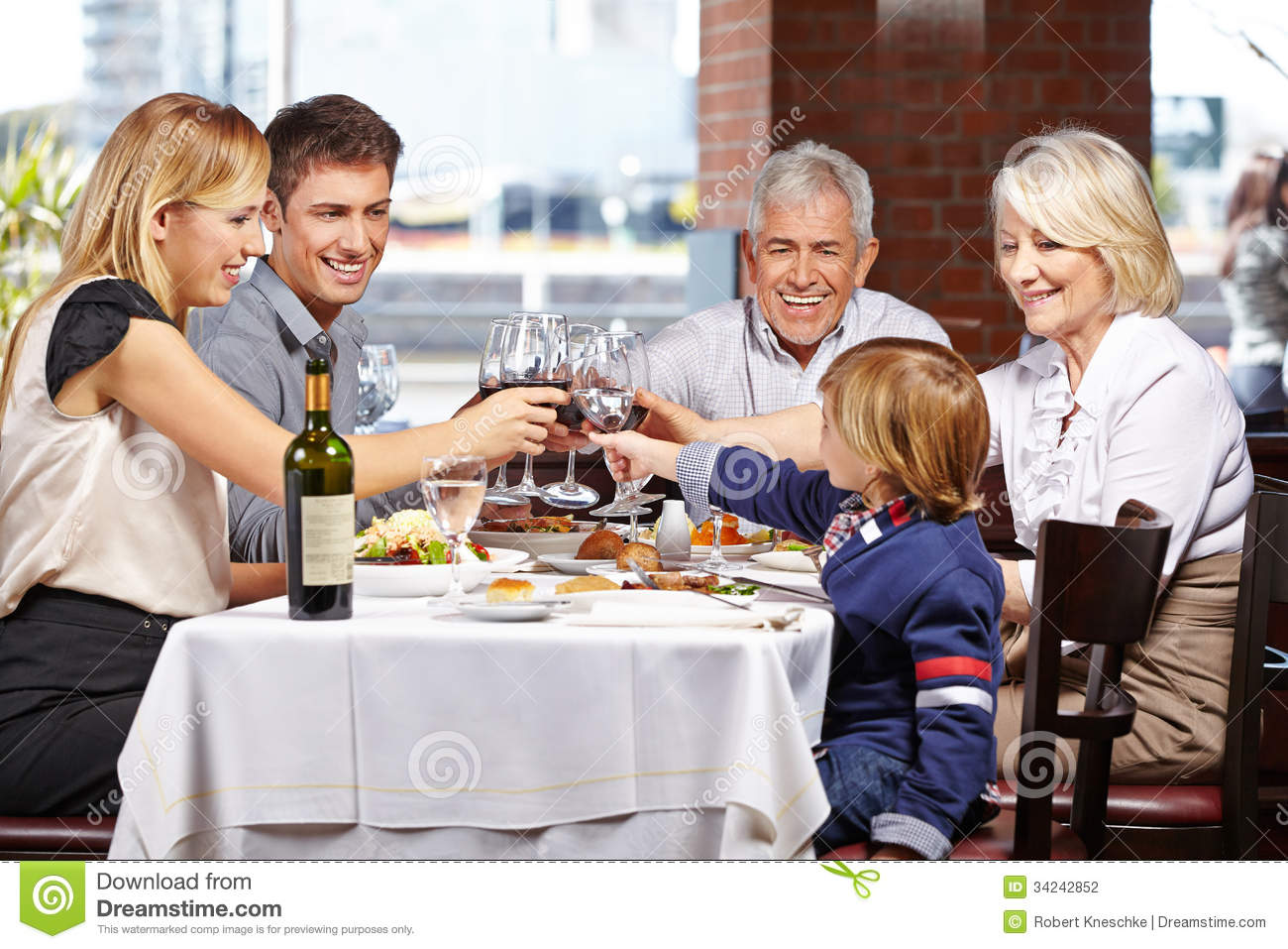 Family In Restaurant Clinking