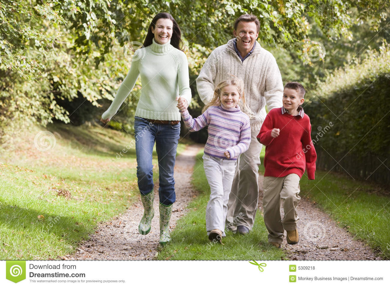 Family running along woodland track