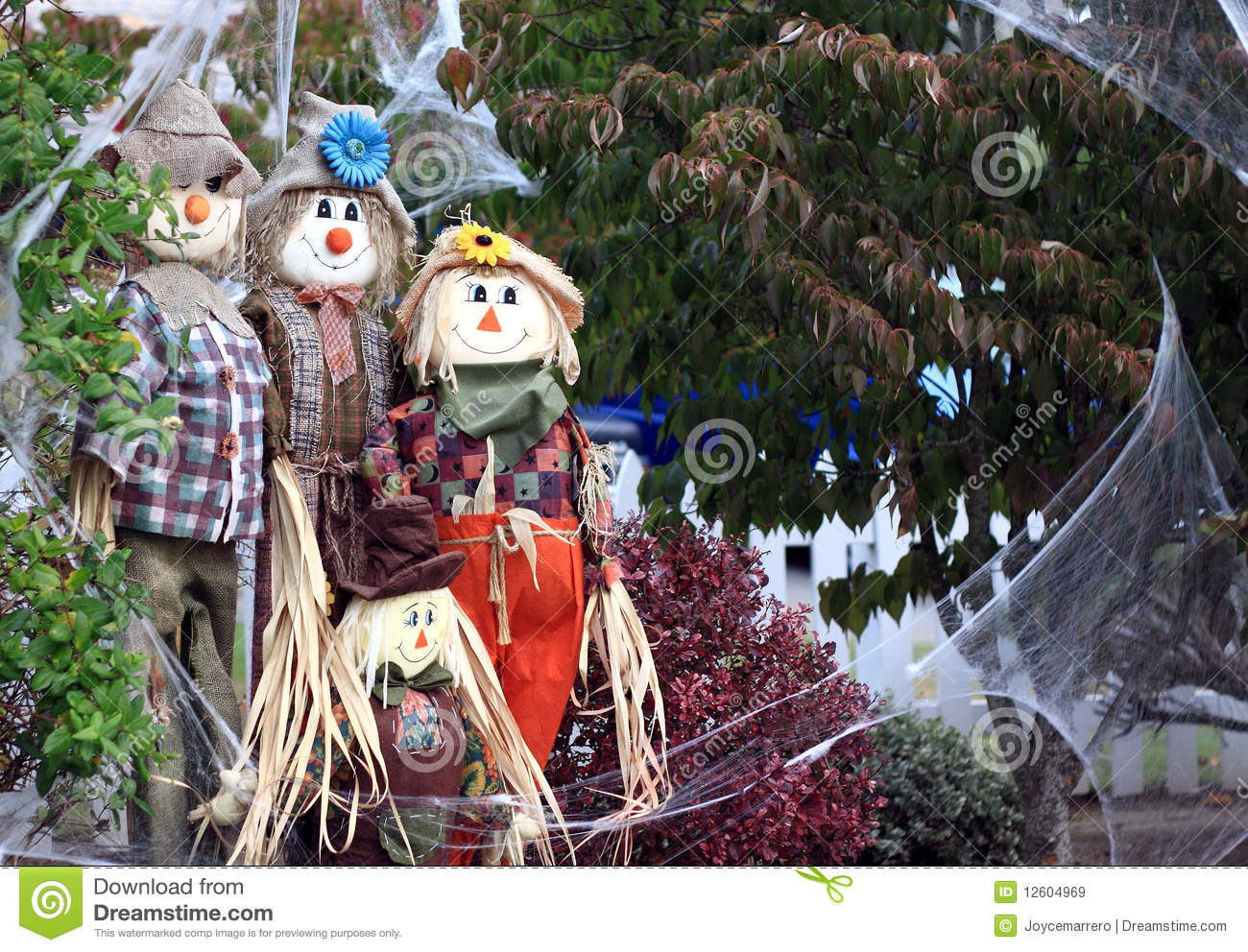 Group of scarecrows surrounded by fake spiderweb in an outdoor yard ...