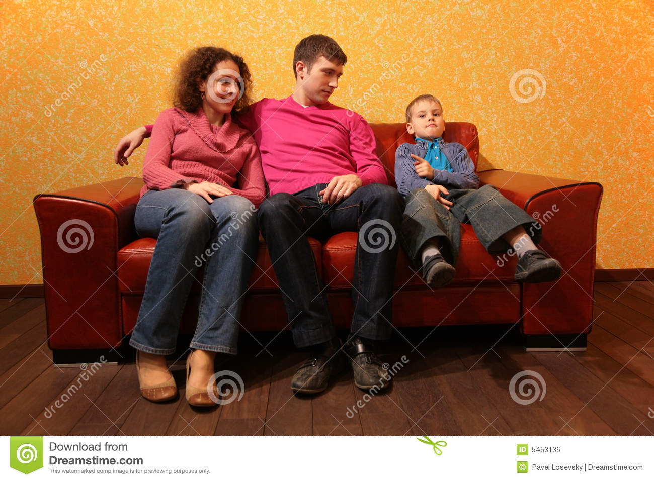 Family Seating On Red Leather Sofa Royalty Free Stock