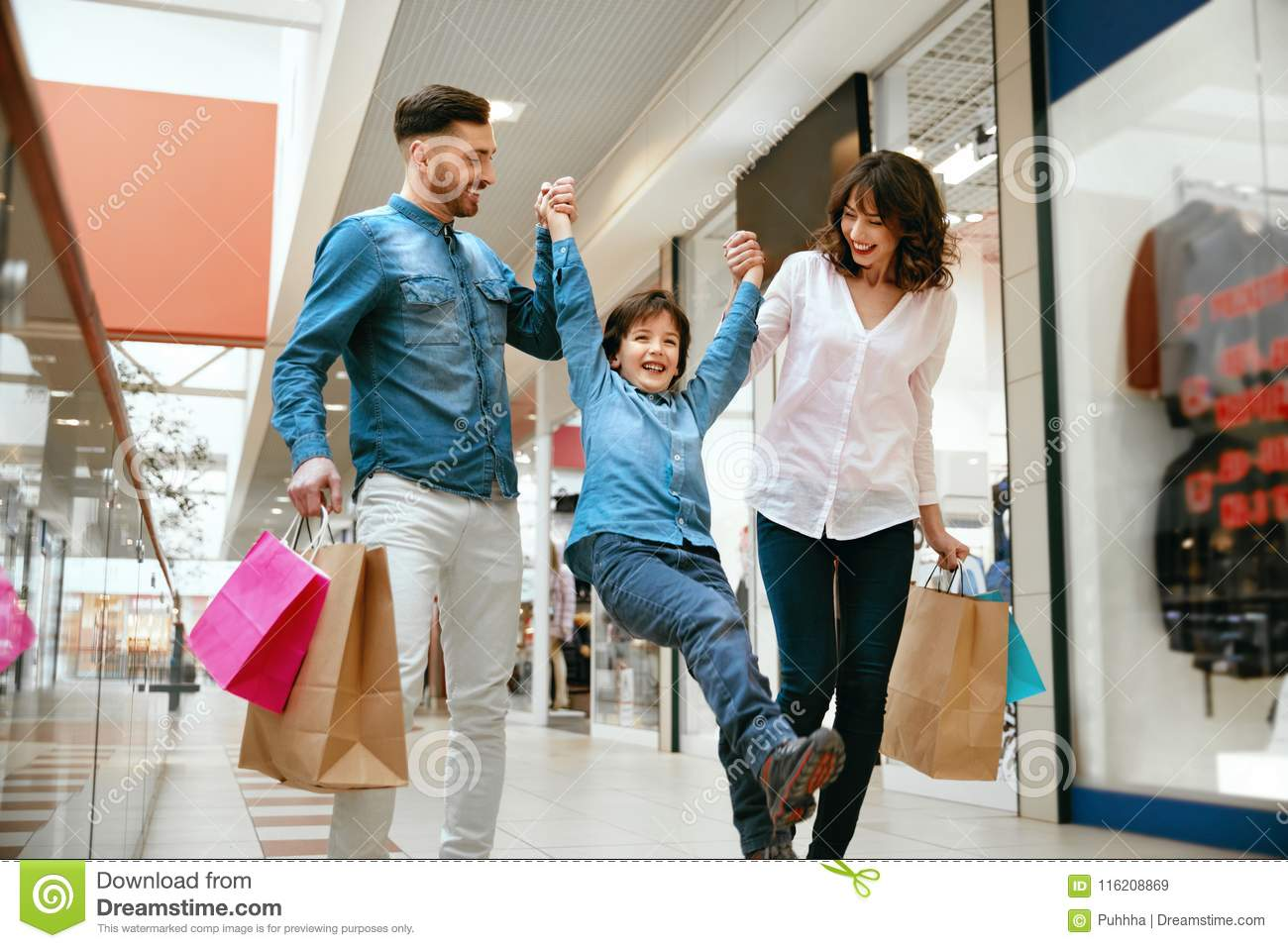 68313b4ad Family Shopping. Happy People With Child Carrying Bags, Walking In Modern  Mall. High Resolution.