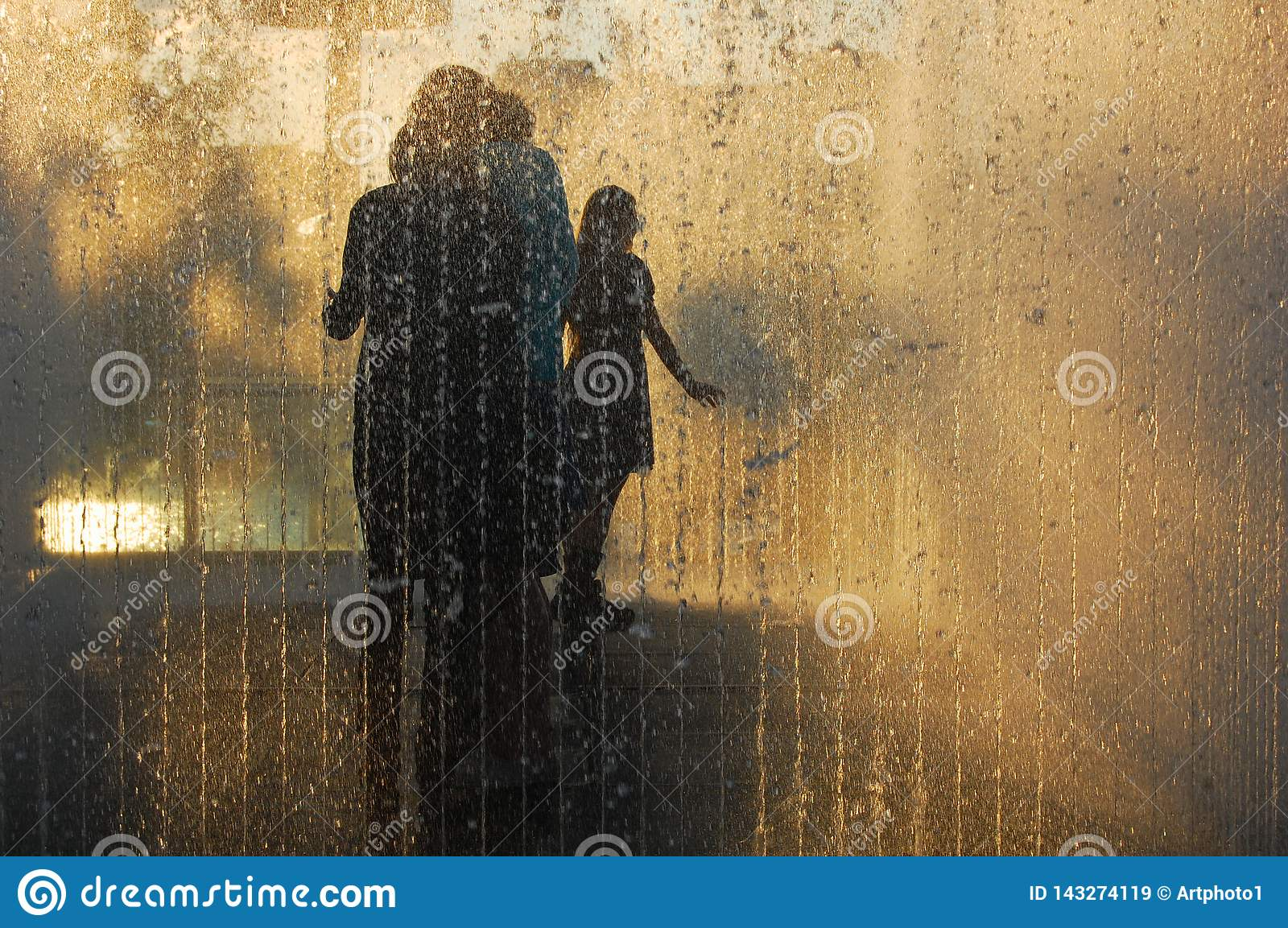 Family in silhouette enjoy pavement fountain