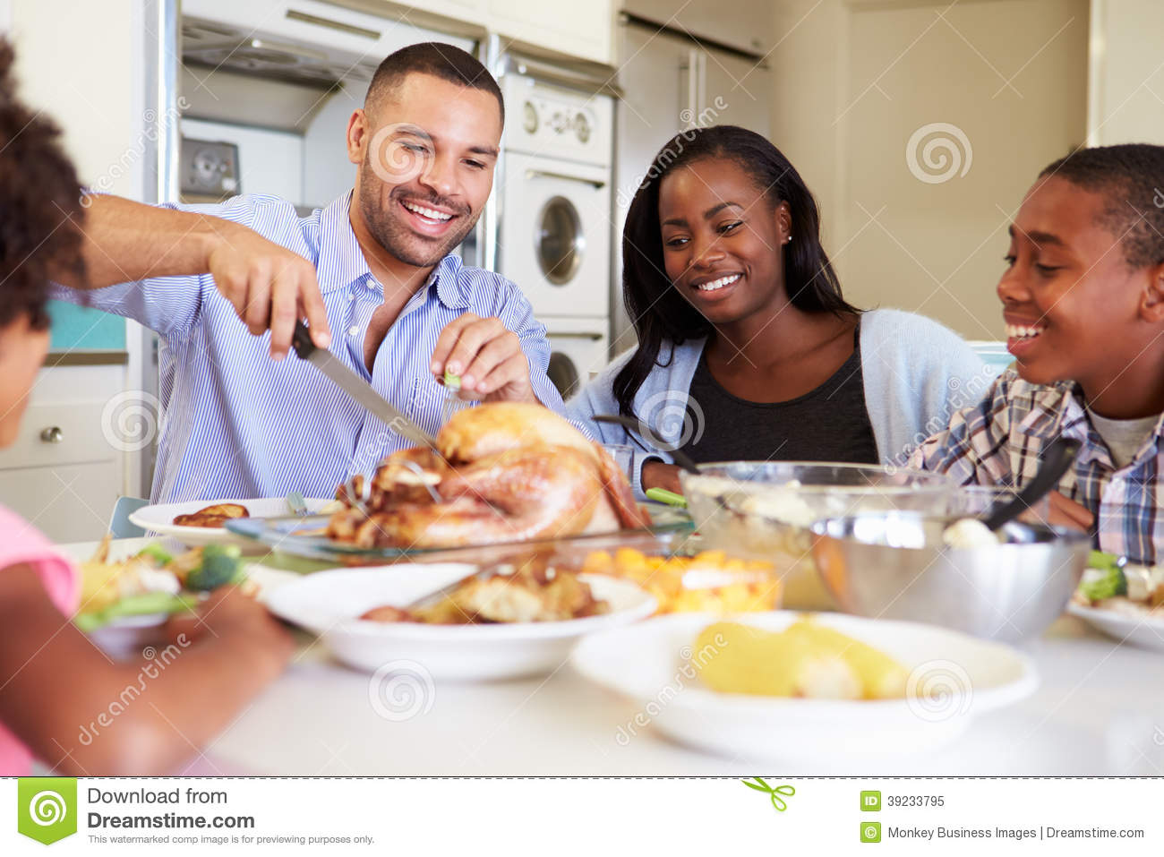 Family sitting around table at home eating meal stock for Eating table