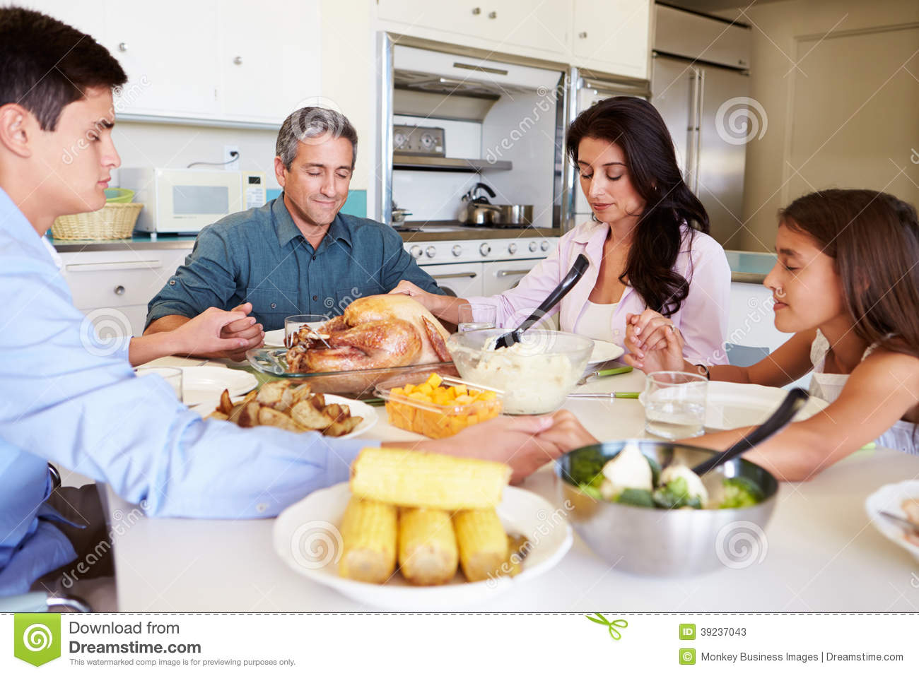Family sitting around table saying prayer before eating for Eating table
