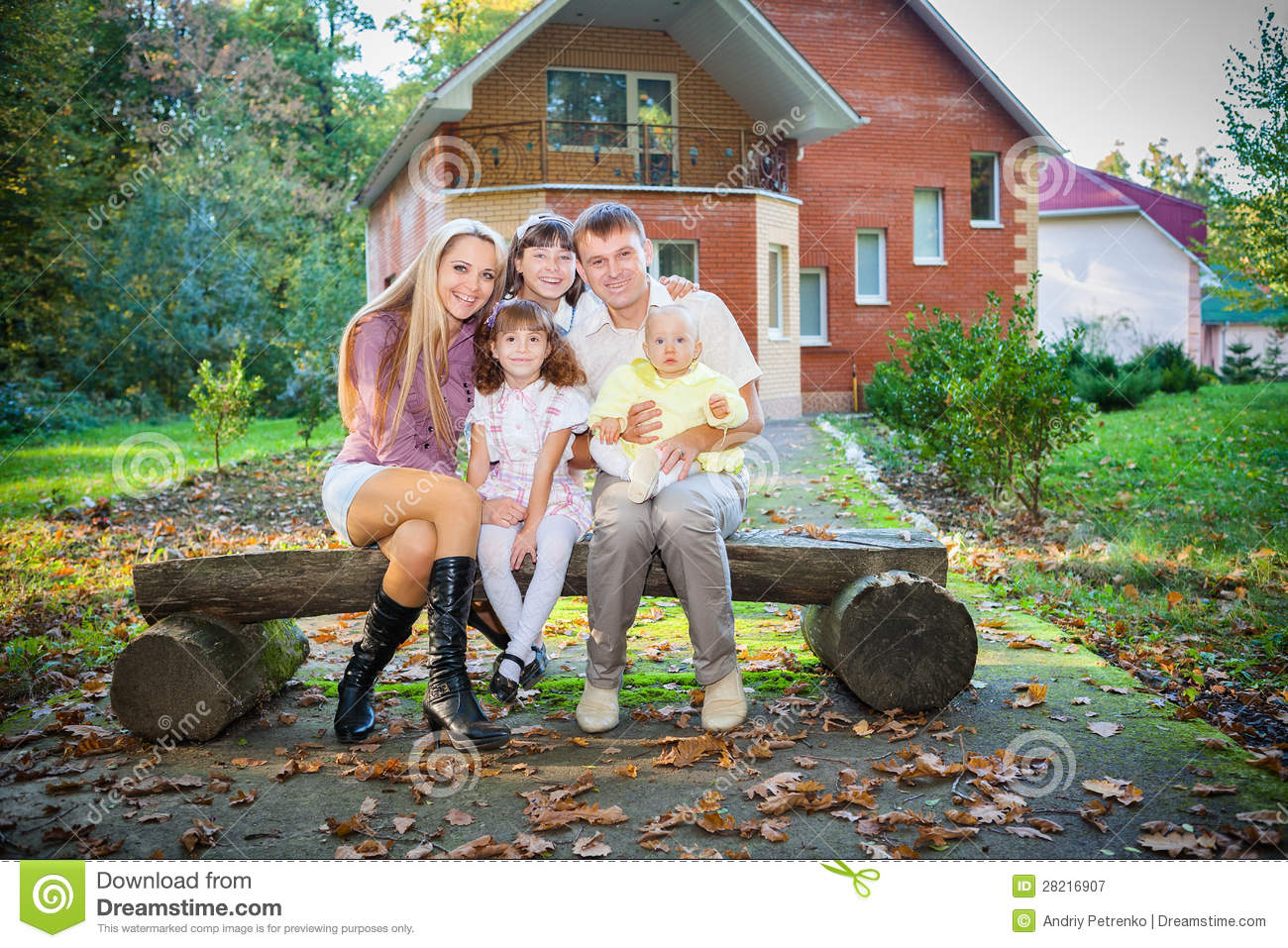 happy family sitting in backyard of new home