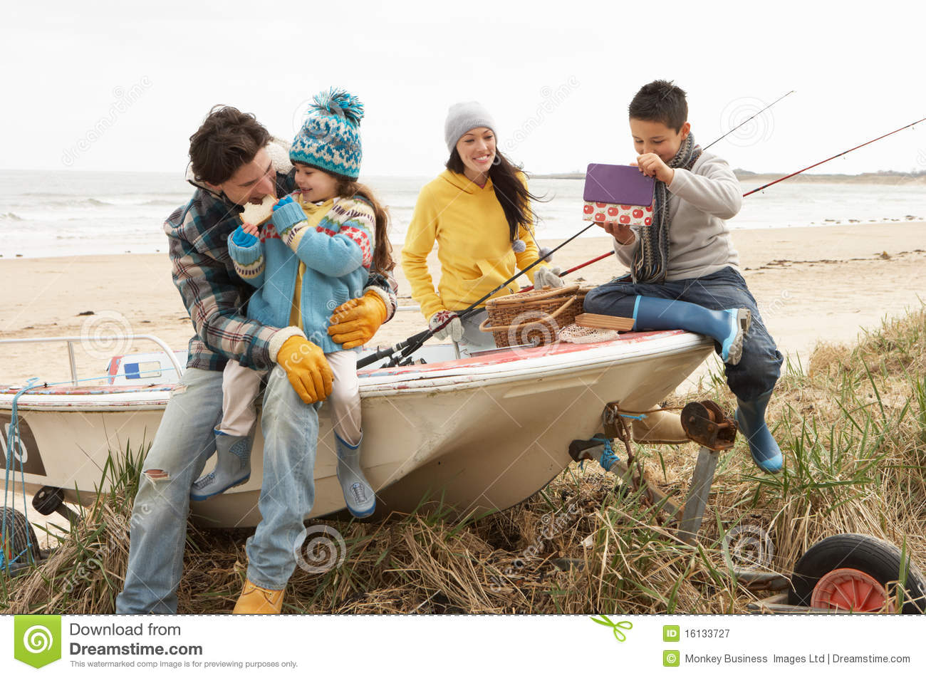 Family sitting on boat with fishing rod on beach stock for Fishing times free