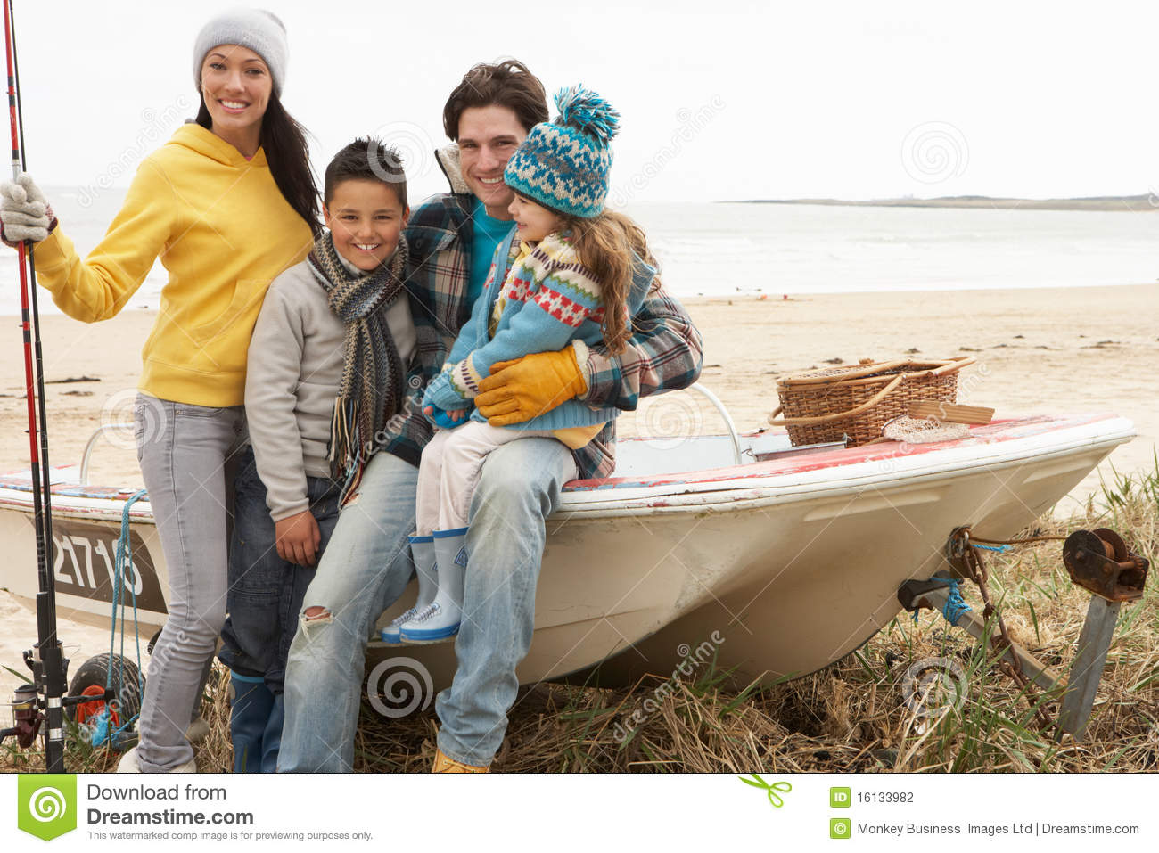 Family sitting on boat with fishing rod on beach stock for Best boat for fishing and family fun