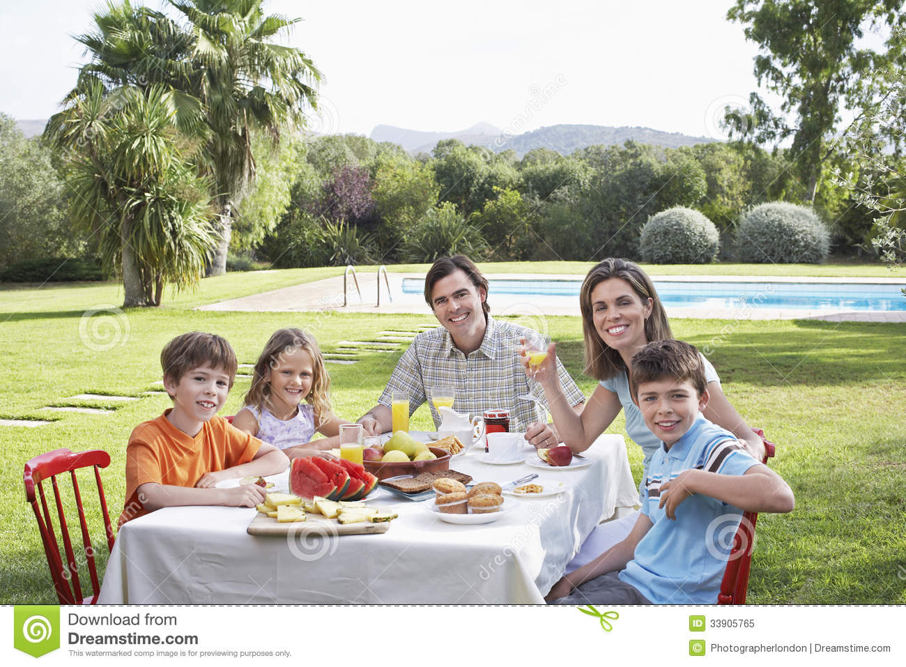Family Sitting At Breakfast Table In Garden Royalty Free