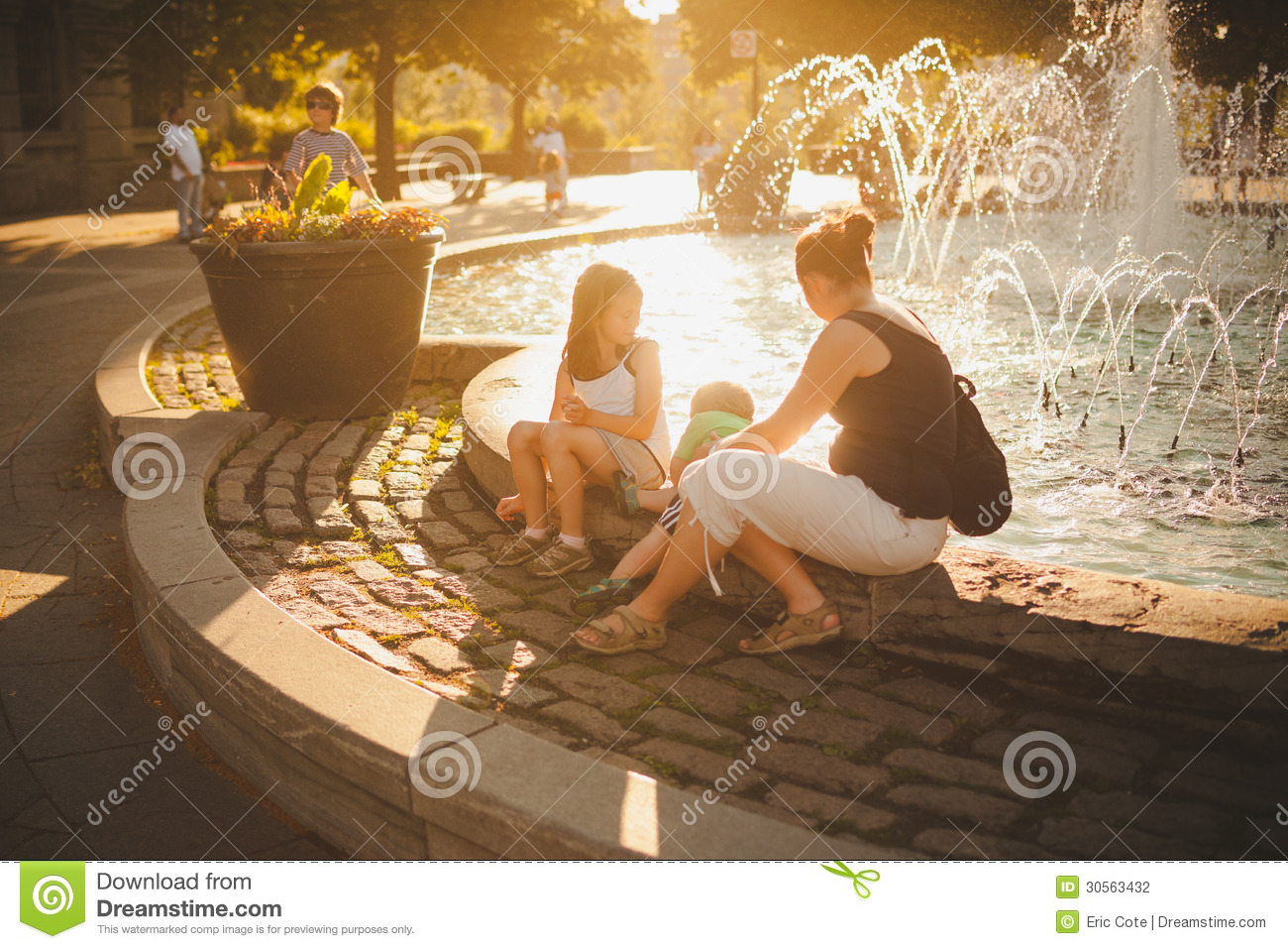Family sitting by a fountain