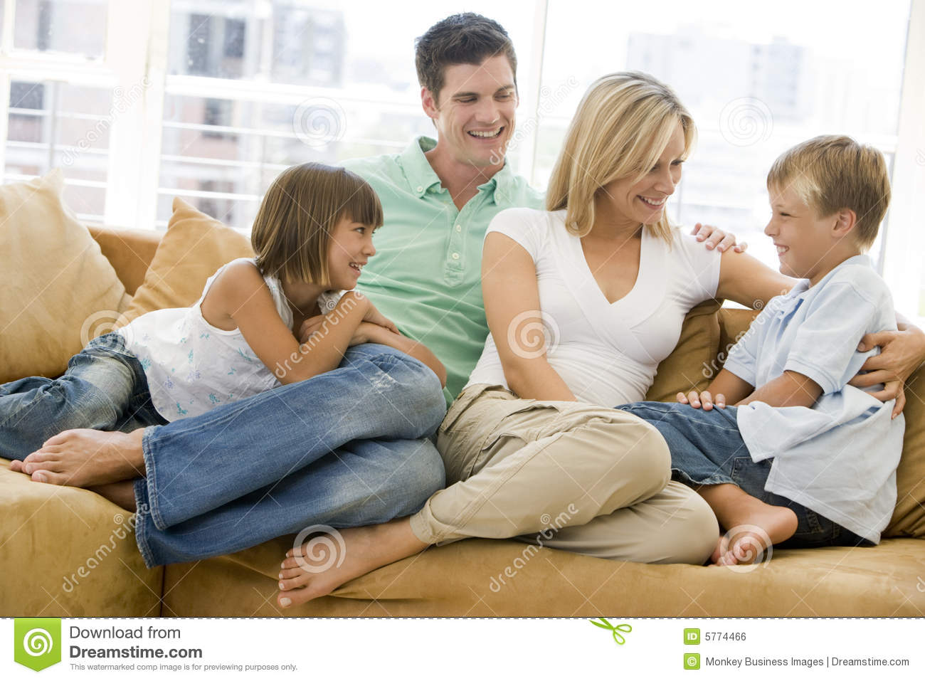 Family sitting in living room smiling stock photo image for Family in a living room