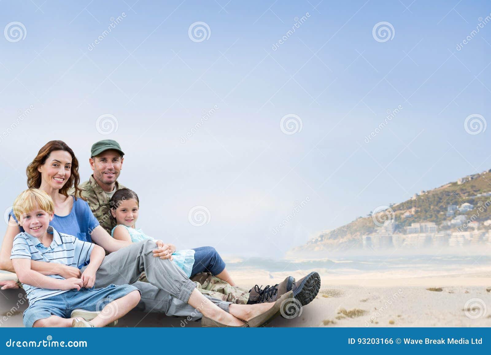 Family sitting on sand against coastline background