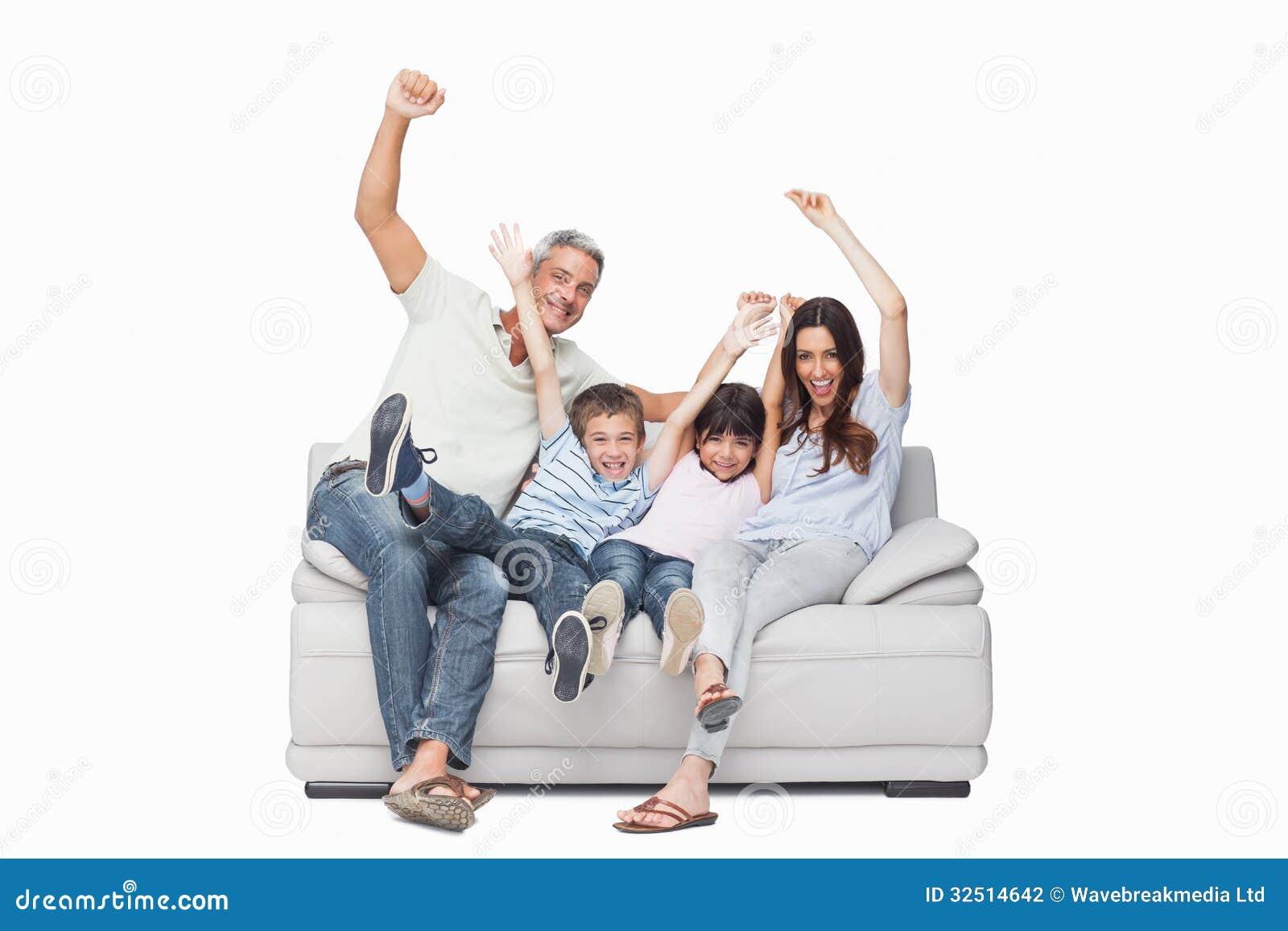 Family Sitting On Sofa Raising Their Arms Stock